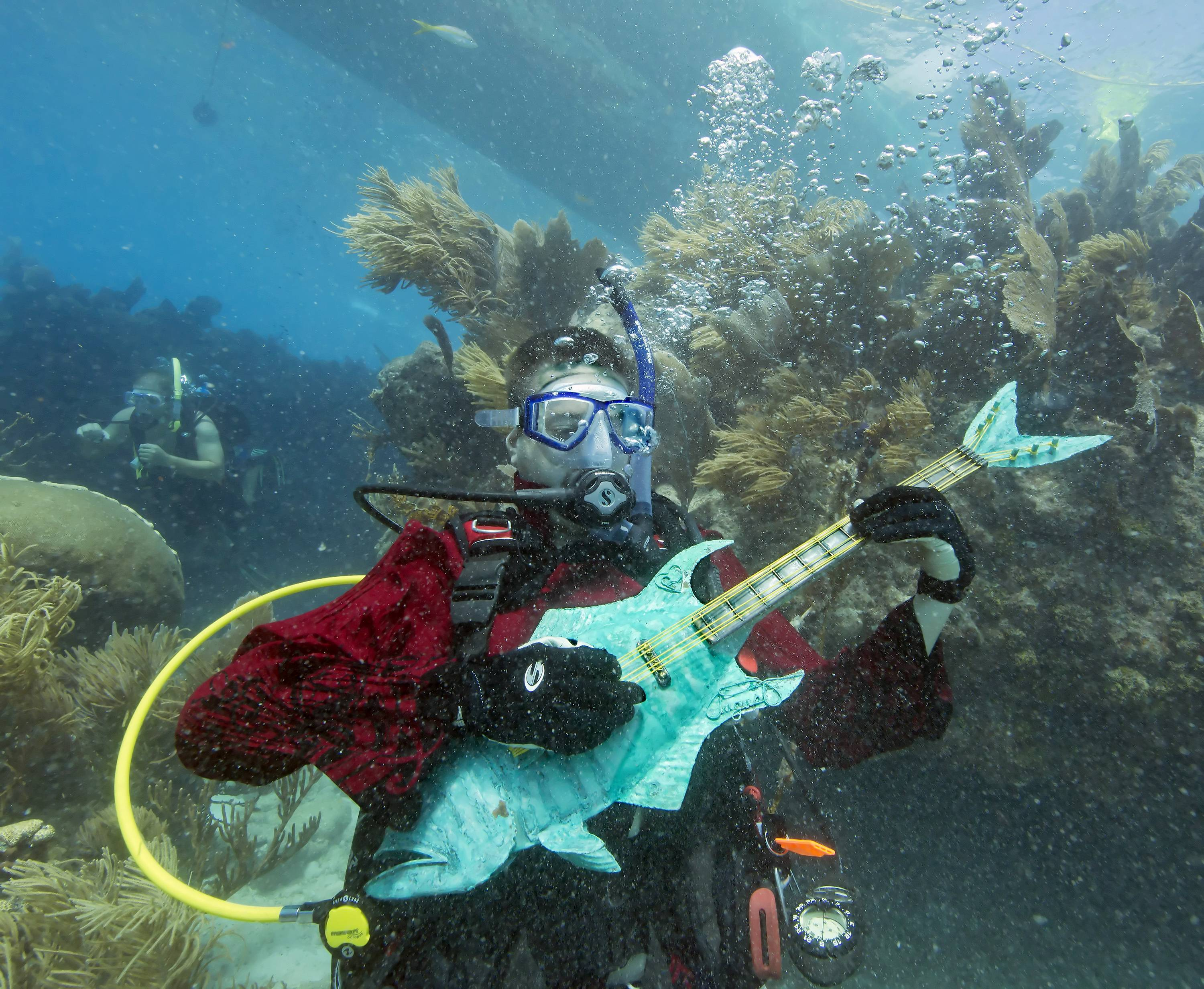 Mike Limerick pretends to play a mock musical instrument Saturday at the Lower Keys Underwater Music Festival, in the Florida Keys National Marine Sanctuary. The subsea concert at Looe Key Reef, about six miles south of Big Pine Key, Fla., attracted almost 500 divers and snorkelers to listen to a local radio station's four-hour broadcast piped beneath the sea via underwater speakers.