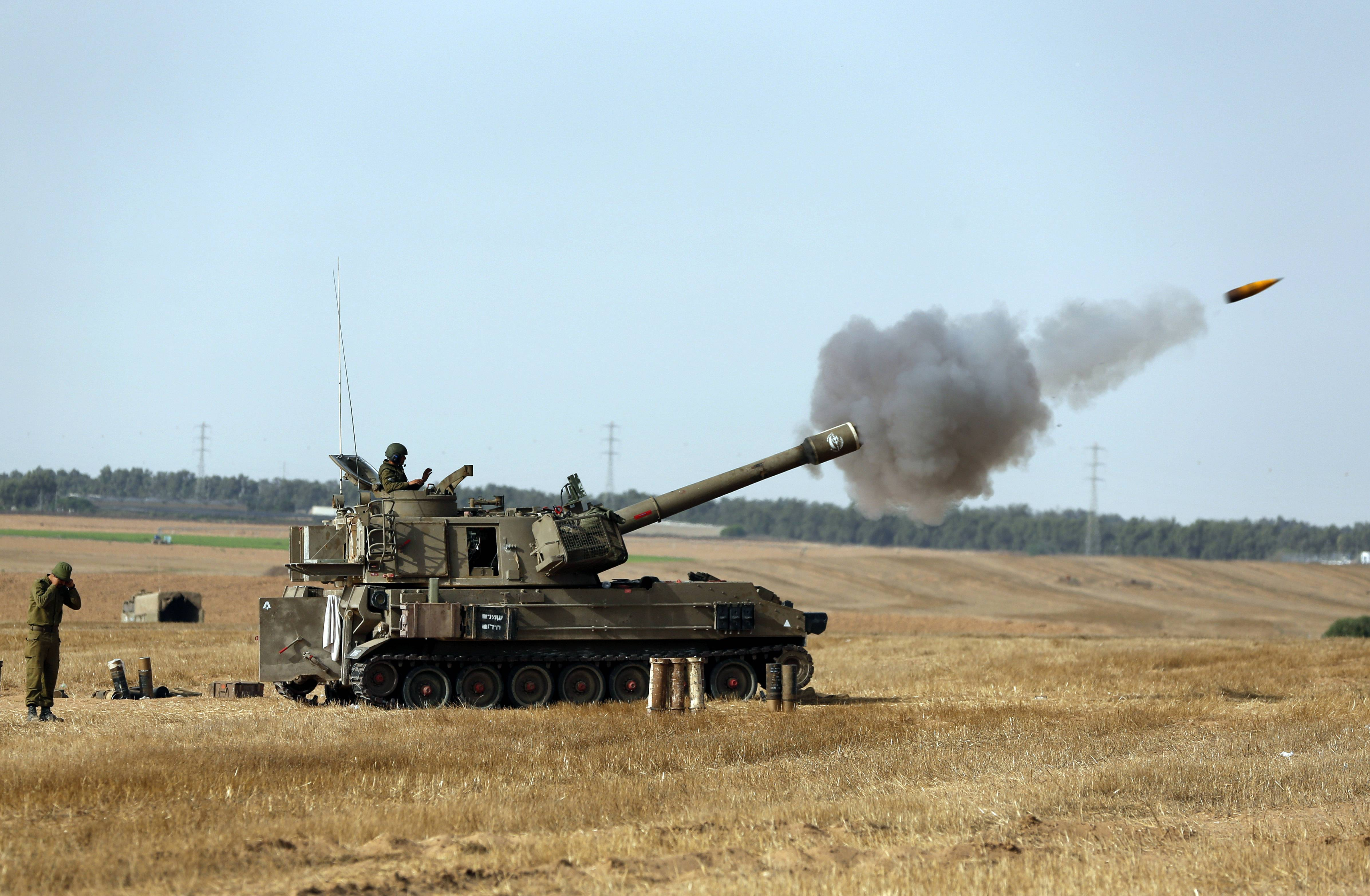 Israeli soldiers on a mobile artillery unit fire a shell Saturday toward Gaza.