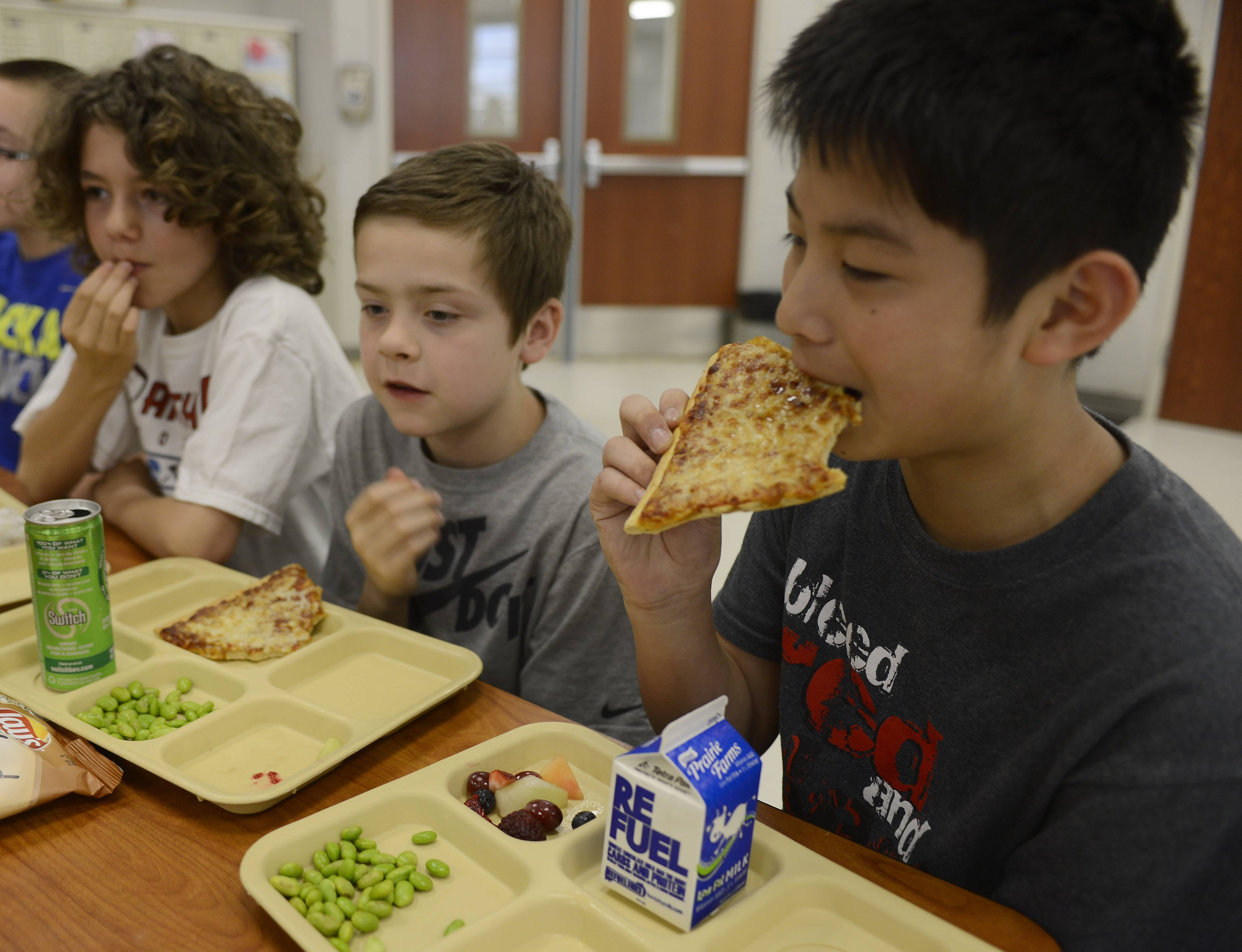 Fifth-graders, from left, Matthew Callas, Max Thompson and Adam Wess selected fruits and vegetables with their lunch in May at Fremont Intermediate School near Mundelein. The school district allows students to have sweet treats as long as healthy food is also on the table.
