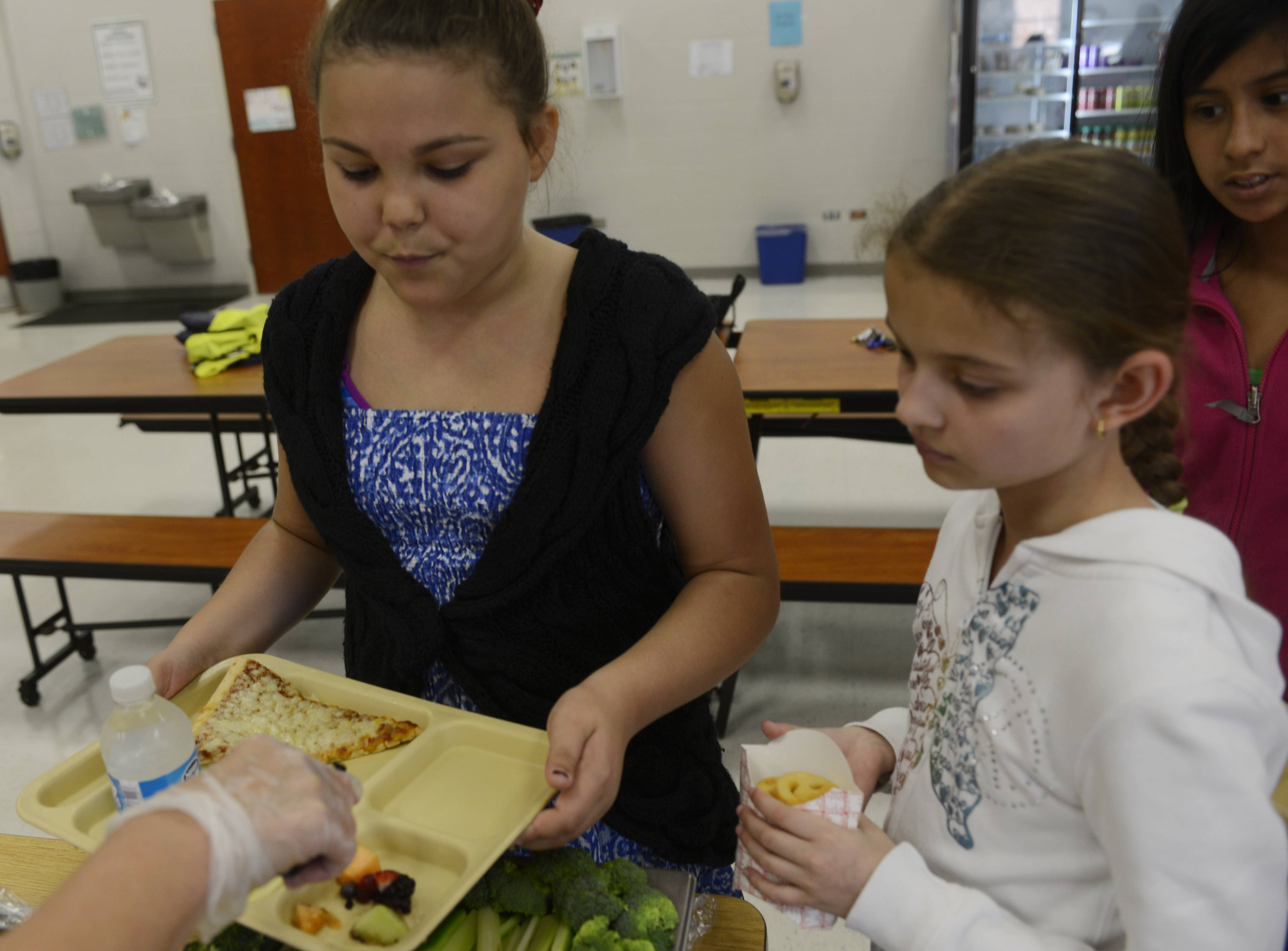 Fifth-grader Georgie Sanchez receives a selection of vegetables she and classmate Alexandra Ulanovski are served in the lunchroom in the spring at Fremont Intermediate School near Mundelein.