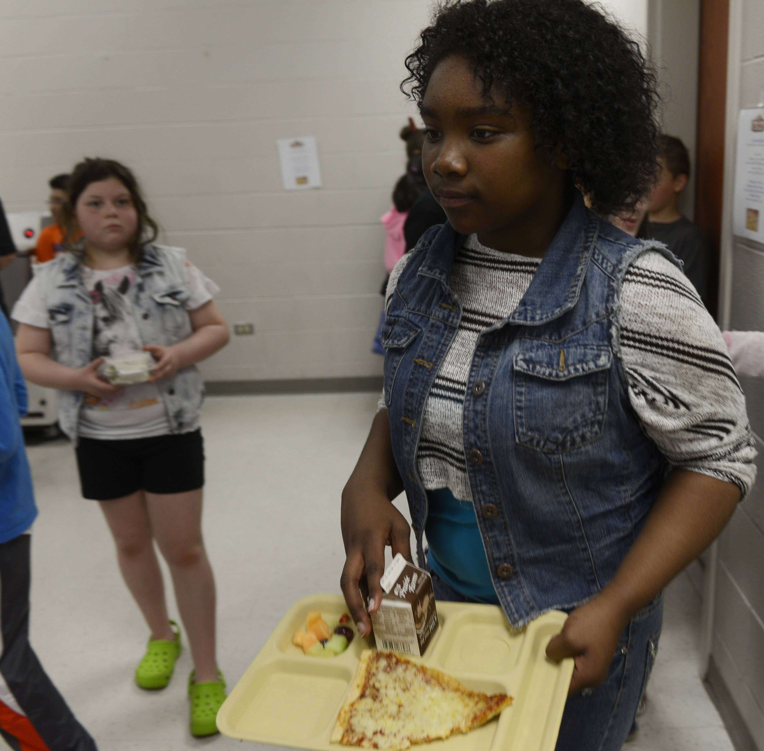 Fifth-grader Kayla Evans has a slice of whole-grain pizza and a serving of fruit on her tray as she makes her way through the lunchroom line in May at Fremont Intermediate School near Mundelein.