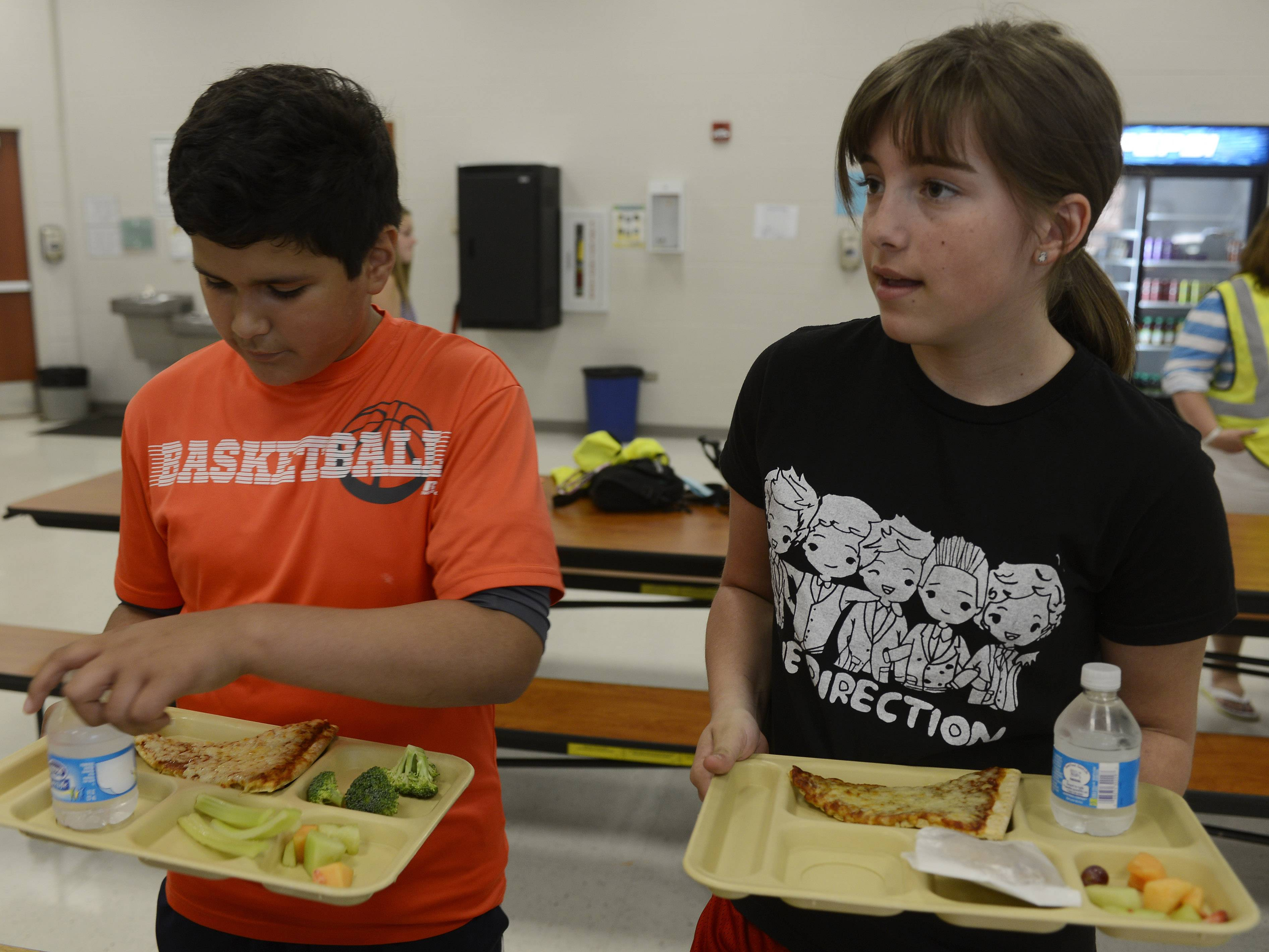 Anthony Martinez and Cheyenne Pellettiere, both fifth-graders, get a serving of vegetables in the lunchroom in May at Fremont Intermediate School near Mundelein. Rather than eliminating sweets, Fremont School District 79 permits students to have them as long as healthy food is also on the table.