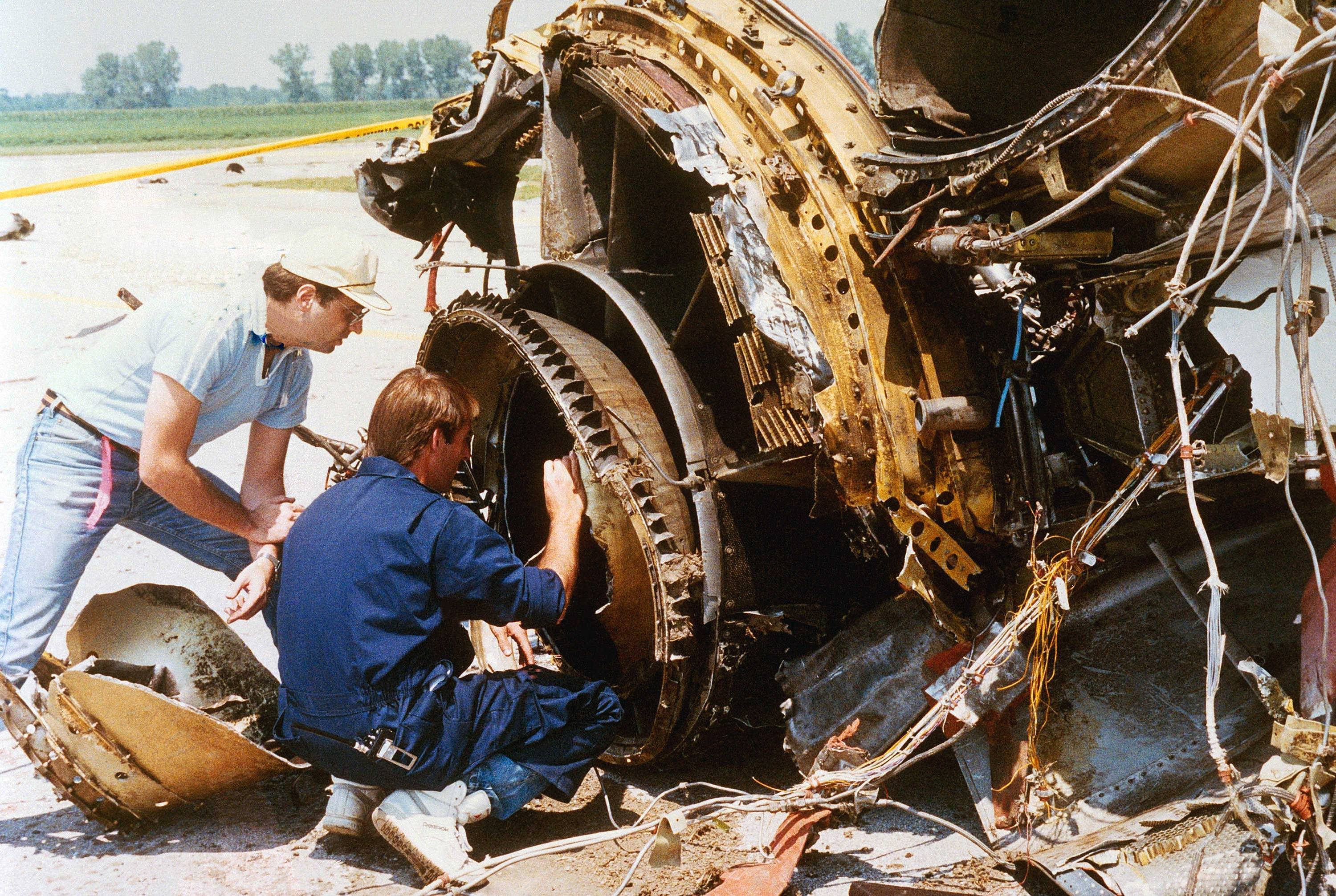 Two National Transportation Safety Board investigators check over the burnt remains of a jet engine from a United Airlines DC-10 in Sioux City, Iowa on July 22, 1989.
