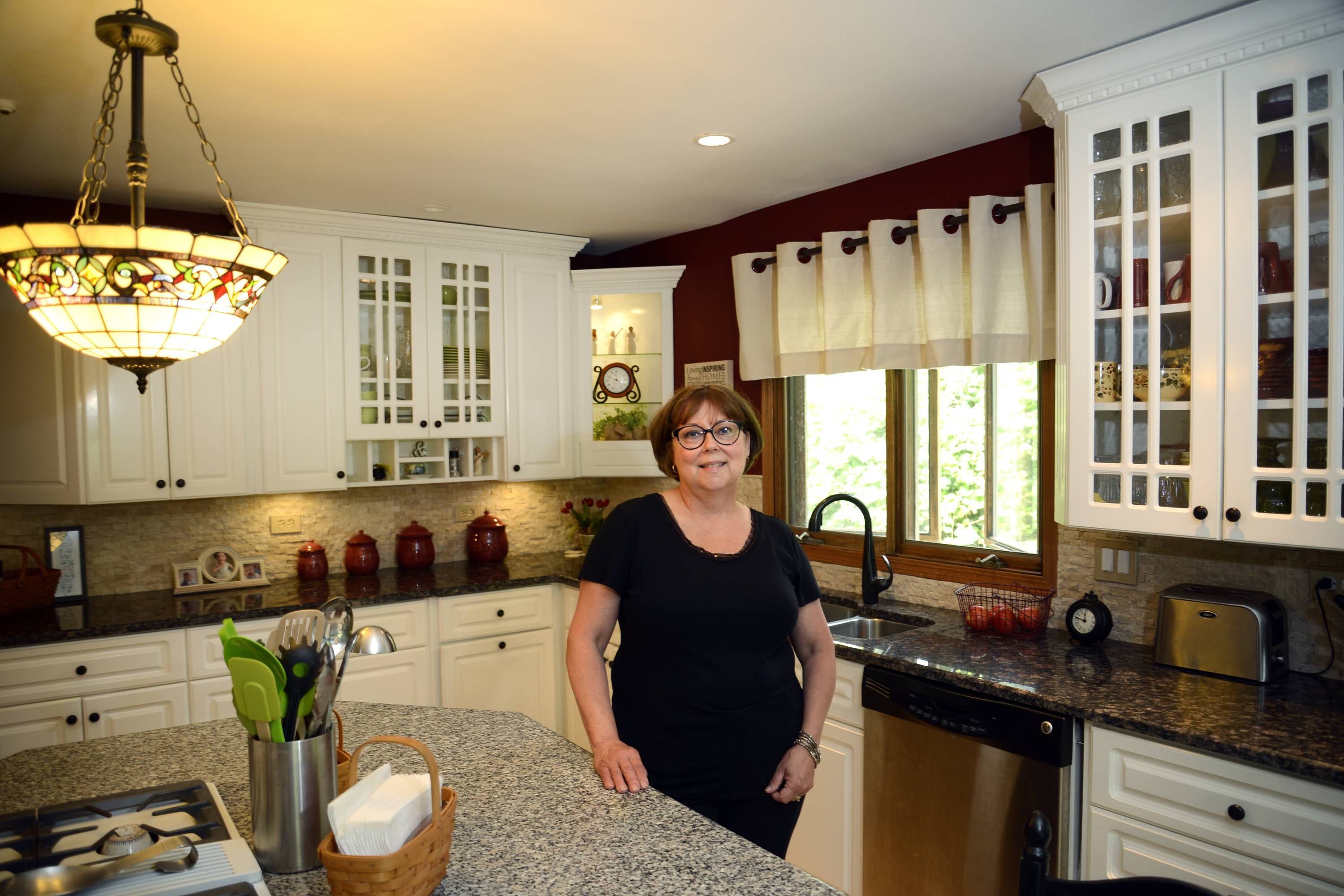 Laurie Parman in her Sleepy Hollow kitchen. She and husband Greg remodeled their home almost exclusively with products from the Elgin ReStore, including cabinetry, countertops, trim, and drop cloths repurposed into curtains.
