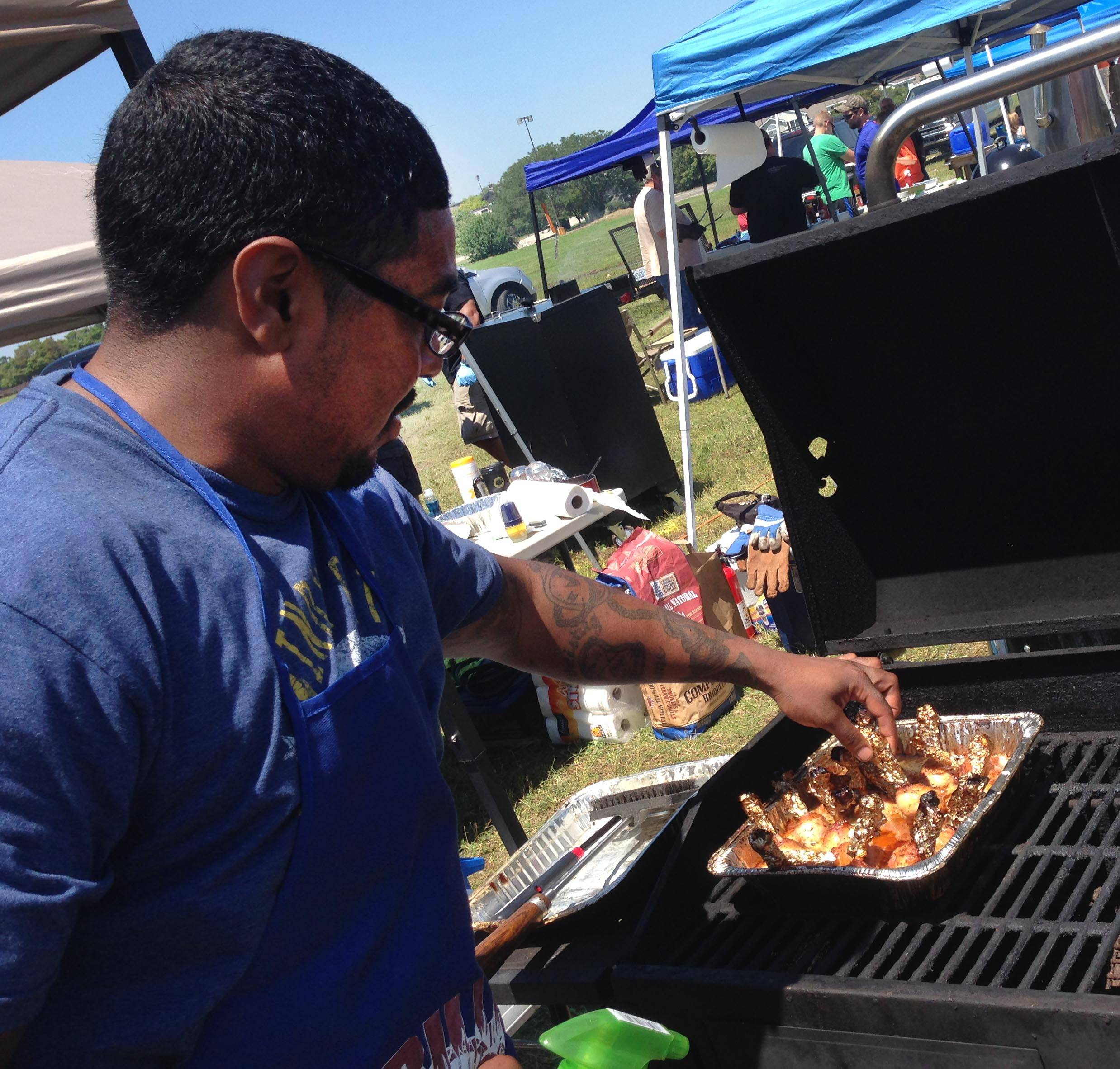 "Garron Thomas of Streamwood checks on his ""lollipop chicken legs"" in one of his three grills Sunday at the Firin' Up The Fox BBQ Competition and Festival in St. Charles."