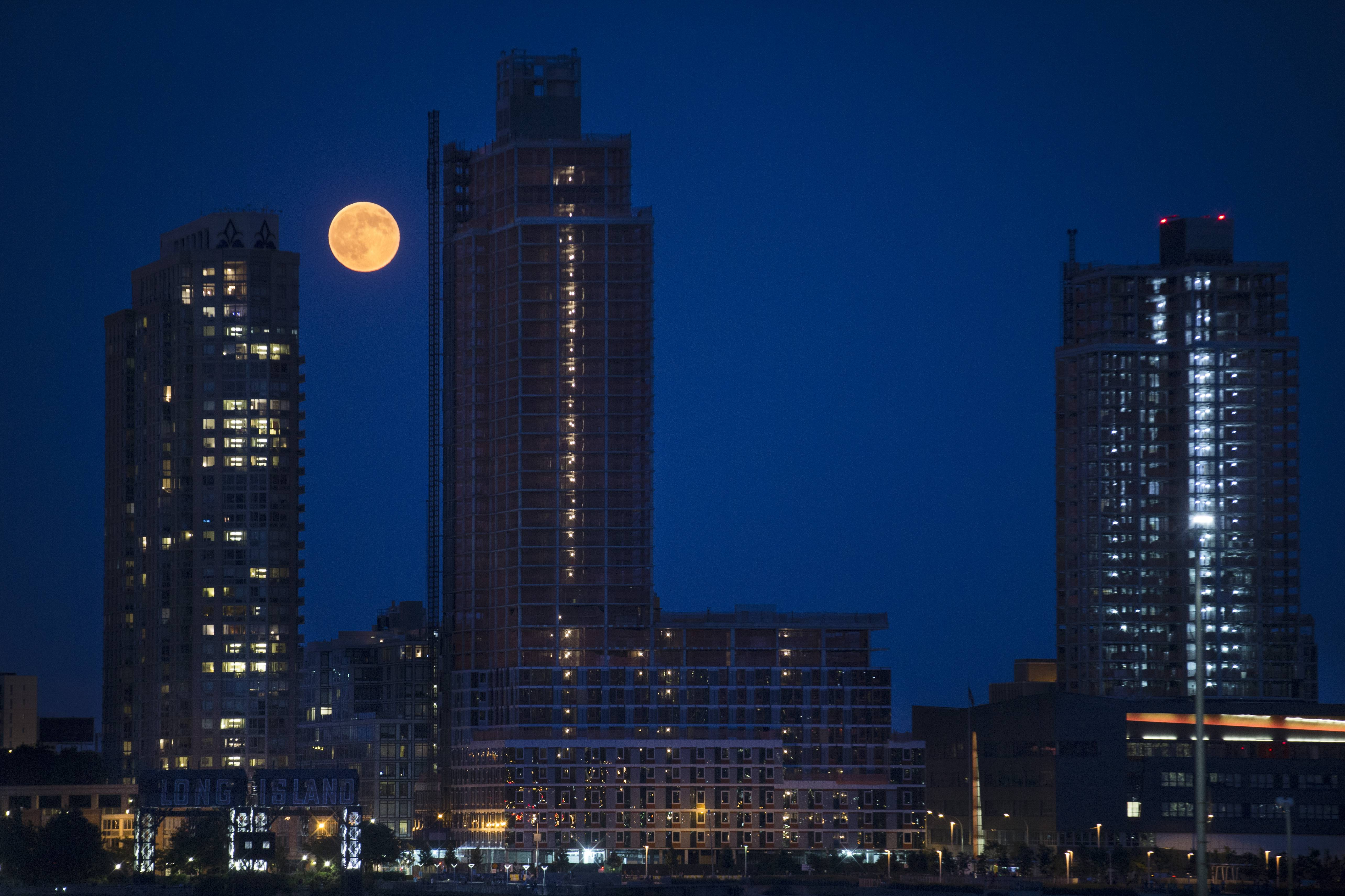 "A perigee moon, also known as a supermoon, rises over the Queens borough of New York, Saturday, July 12, 2014. The phenomenon, which scientists call a ""perigee moon,"" occurs when the moon is near the horizon and appears larger and brighter than other full moons."