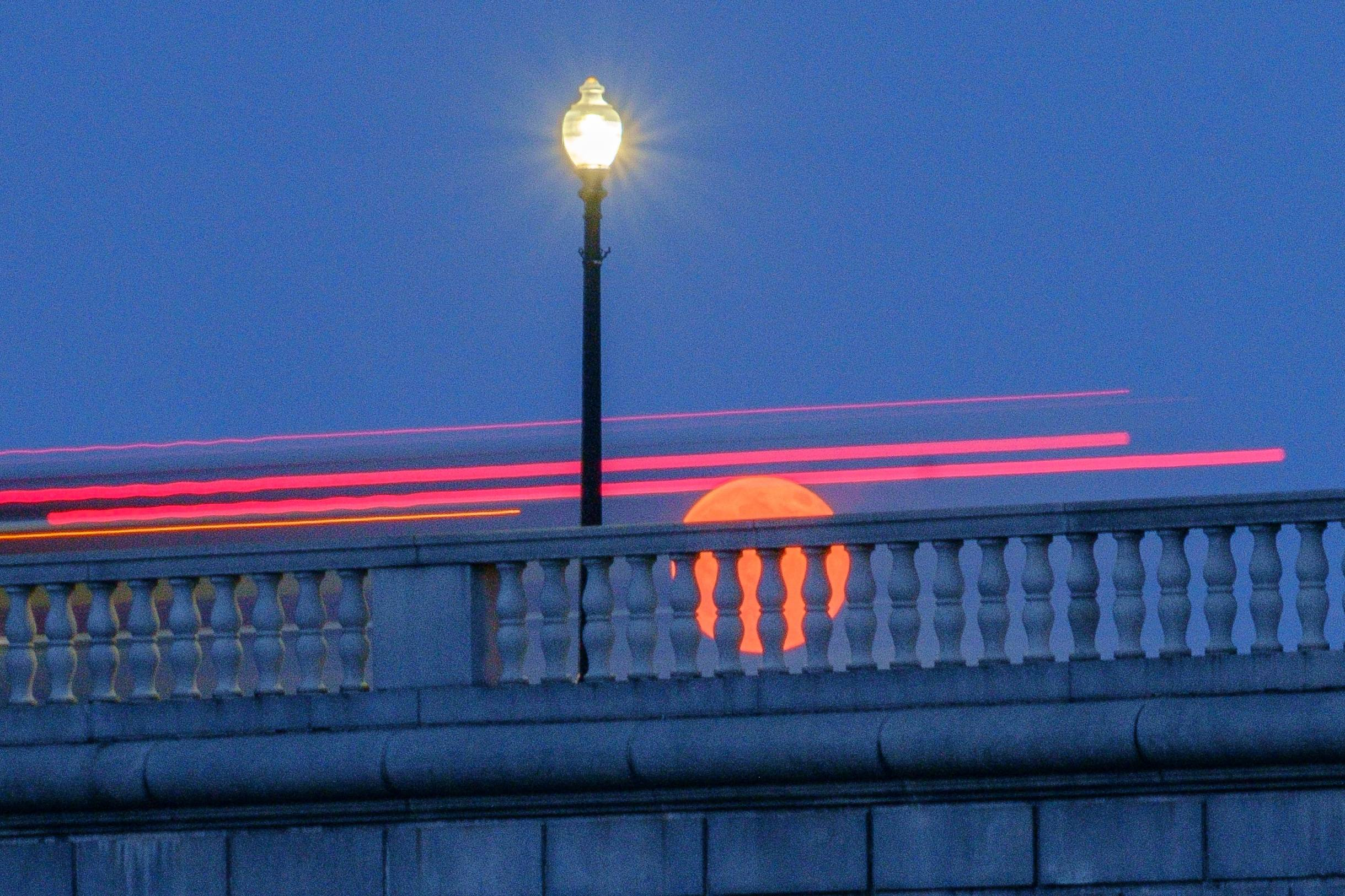 "Traffic streaks by the ""Super Moon"" as it rises behind the Memorial Bridge in Washington, Saturday, July 12, 2014."