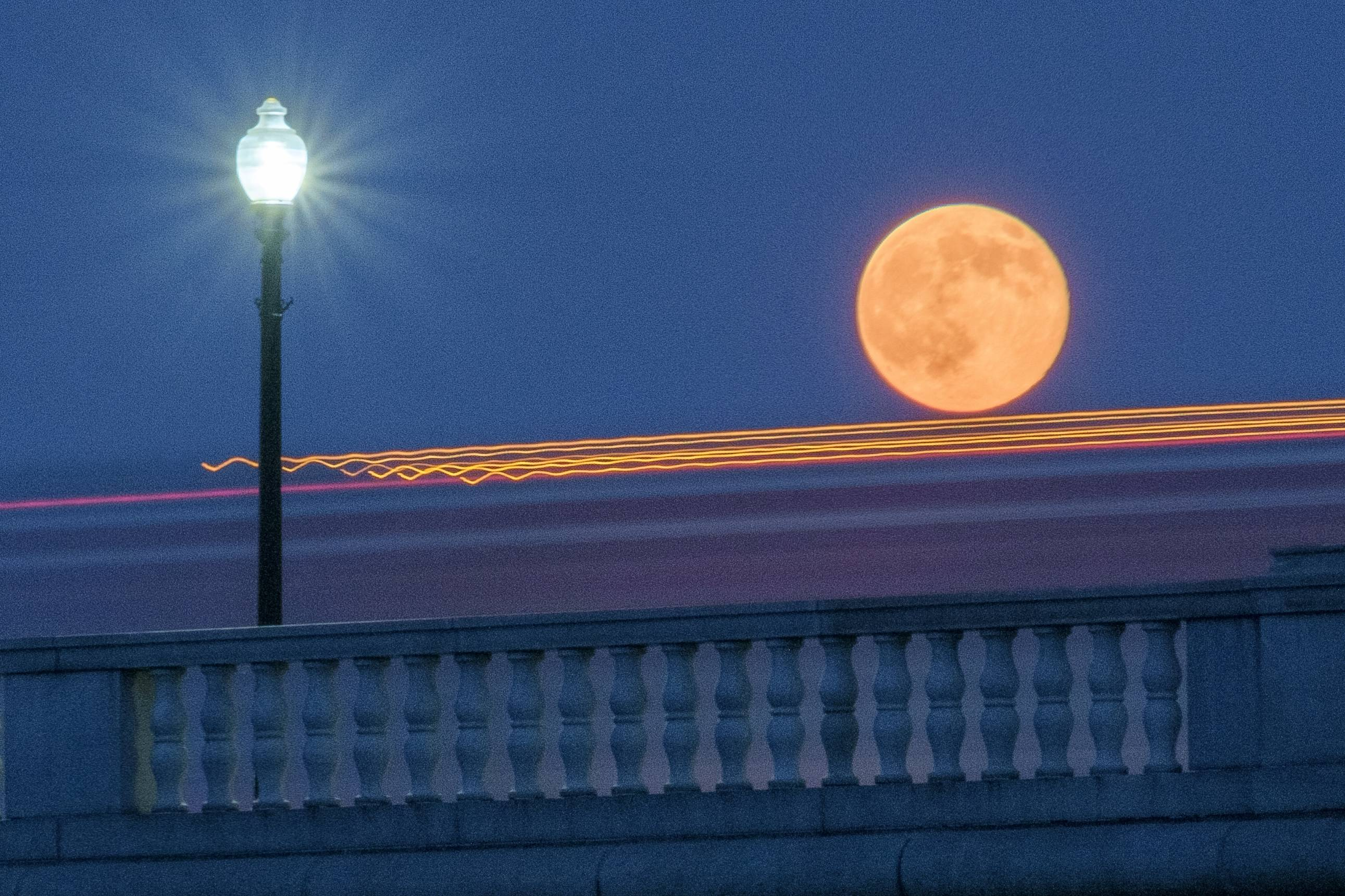 Traffic streaks by the supermoon as it rises behind the Memorial Bridge in Washington, Saturday, July 12, 2014. The full moon Saturday may seem huge, but it's just an illusion caused by its position in the sky.