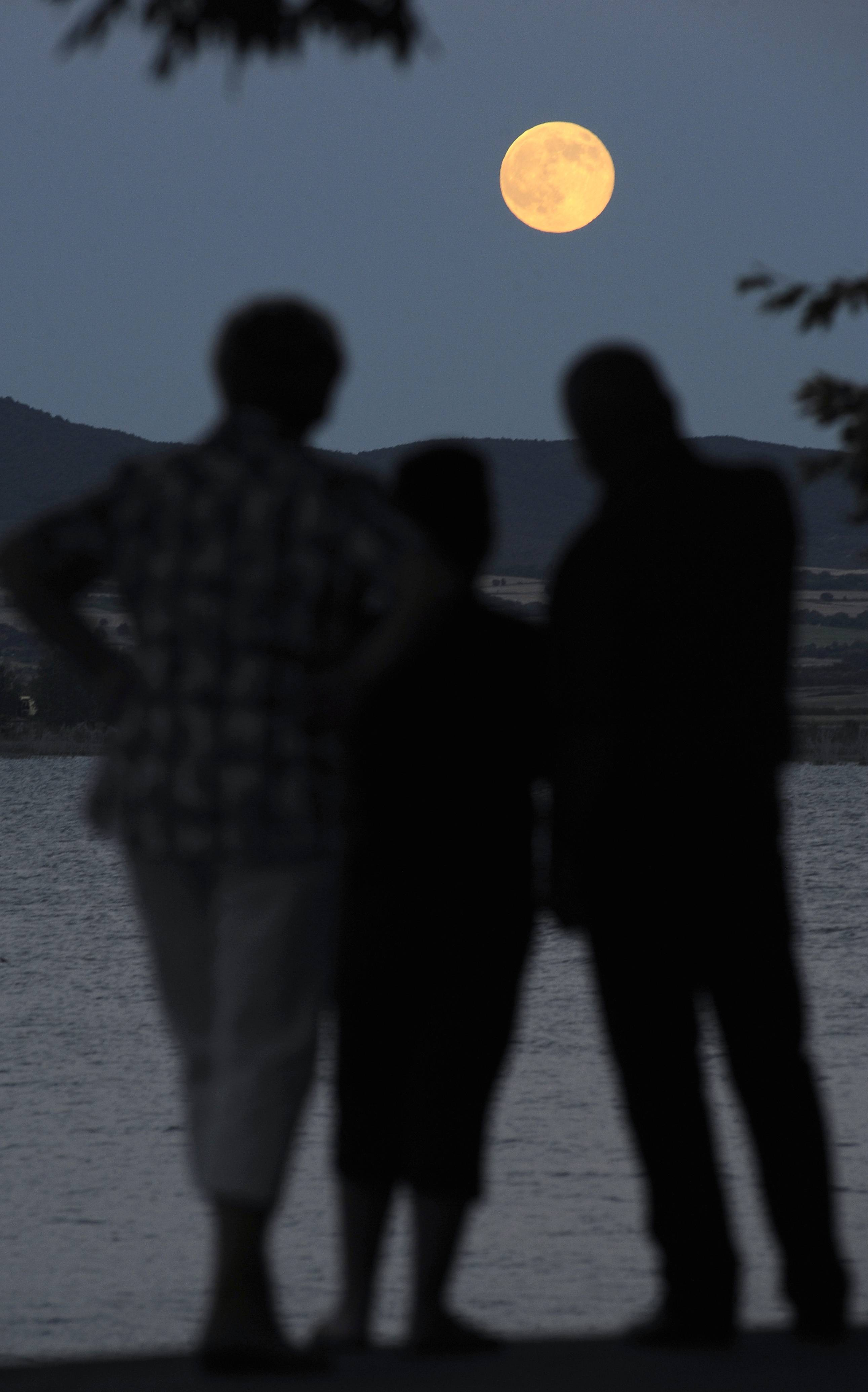 "People look at a perigee moon, also known as a supermoon, rising above Dojran Lake in southeastern Macedonia, on Saturday, July 12, 2014. The phenomenon, which scientists call a ""perigee moon,"" occurs when the moon in its elliptical orbit is relatively close to Earth and seen from the Earth near the horizon, appears larger and brighter than other full moons."