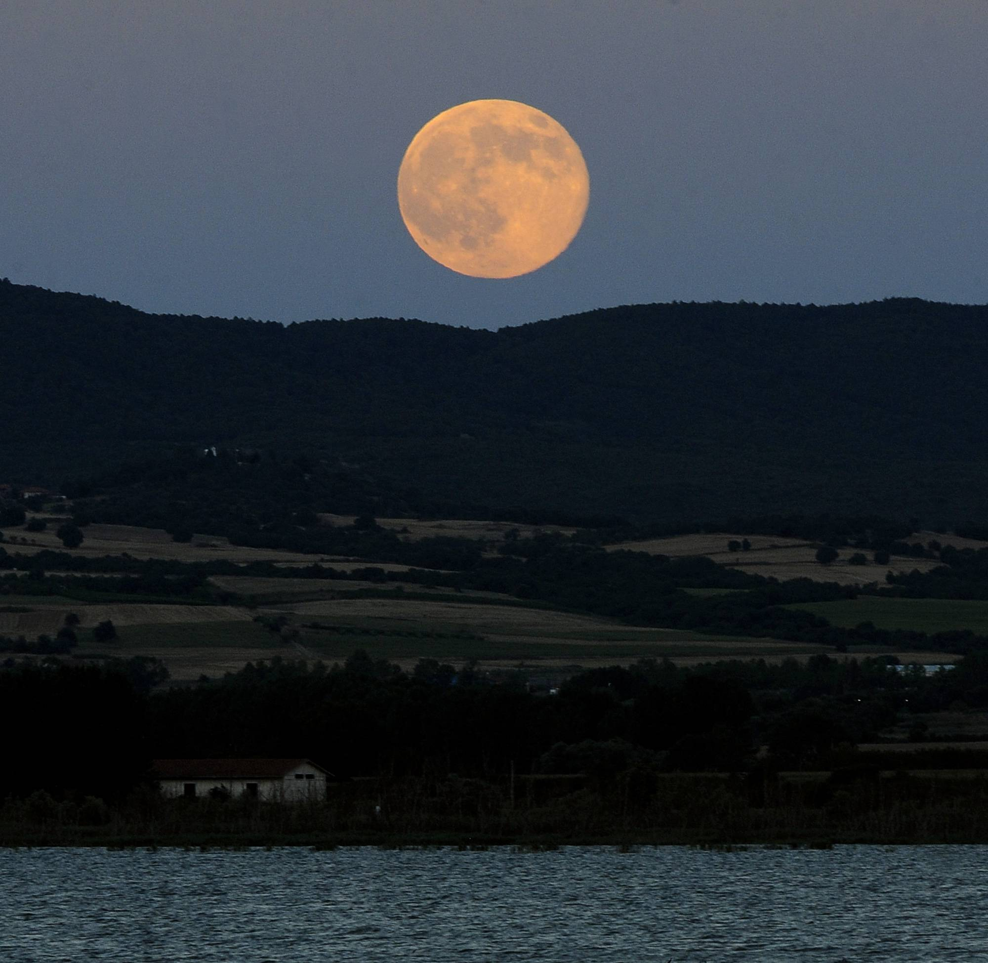 "A perigee moon also known as a supermoon rises above Dojran Lake in southeastern Macedonia, on Saturday, July 12, 2014. The phenomenon, which scientists call a ""perigee moon,"" occurs when the moon in its elliptical orbit is relatively close to Earth and seen from the Earth near the horizon, appears larger and brighter than other full moons."