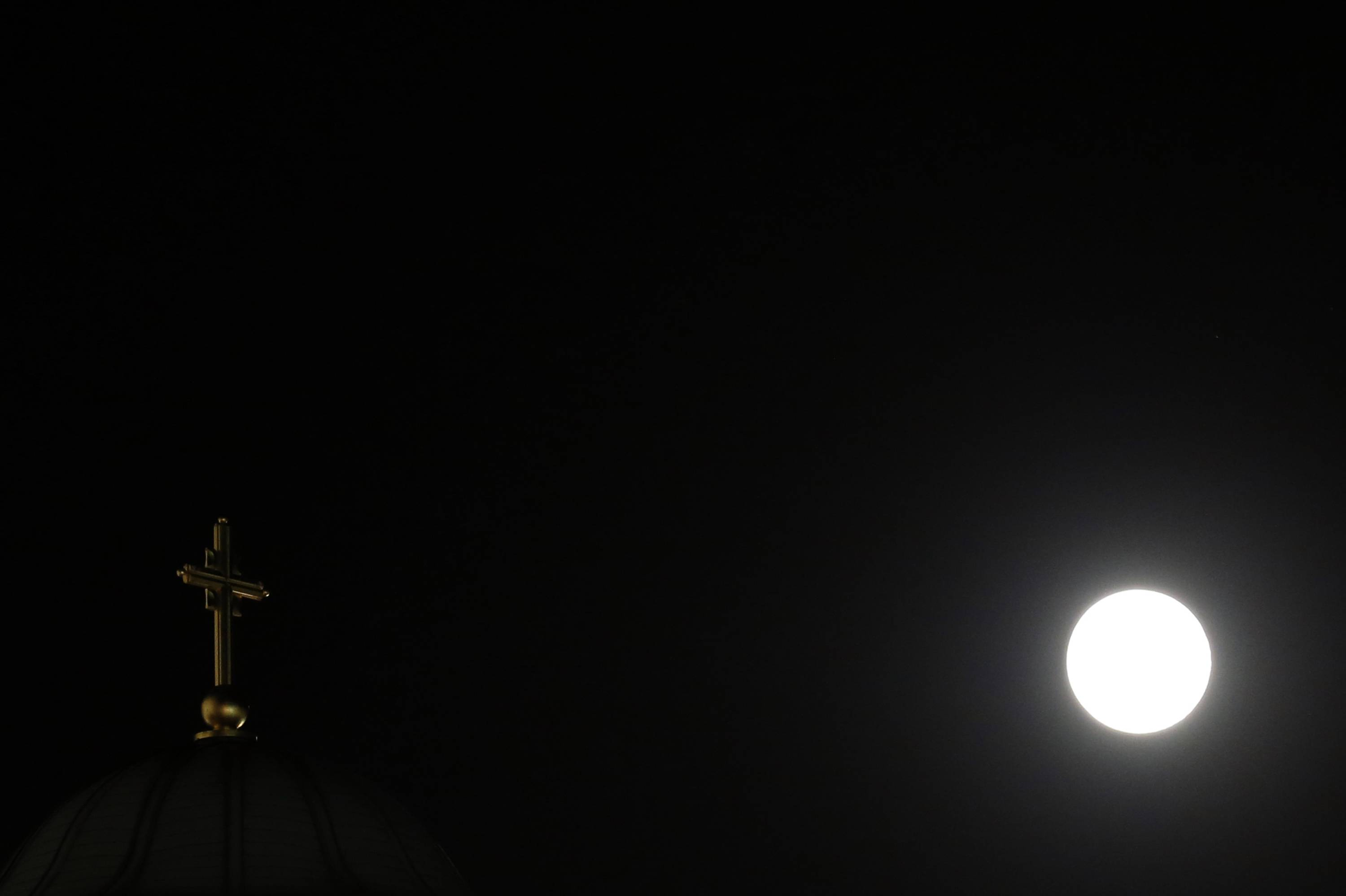 "A perigee moon, also known as a supermoon, is seen behind a traditional Serbian orthodox cross on the St. Sava temple, in Belgrade, Serbia, Saturday, July 12, 2014. The phenomenon, which scientists call a ""perigee moon,"" occurs when the moon is near the horizon and appears larger and brighter than other full moons."