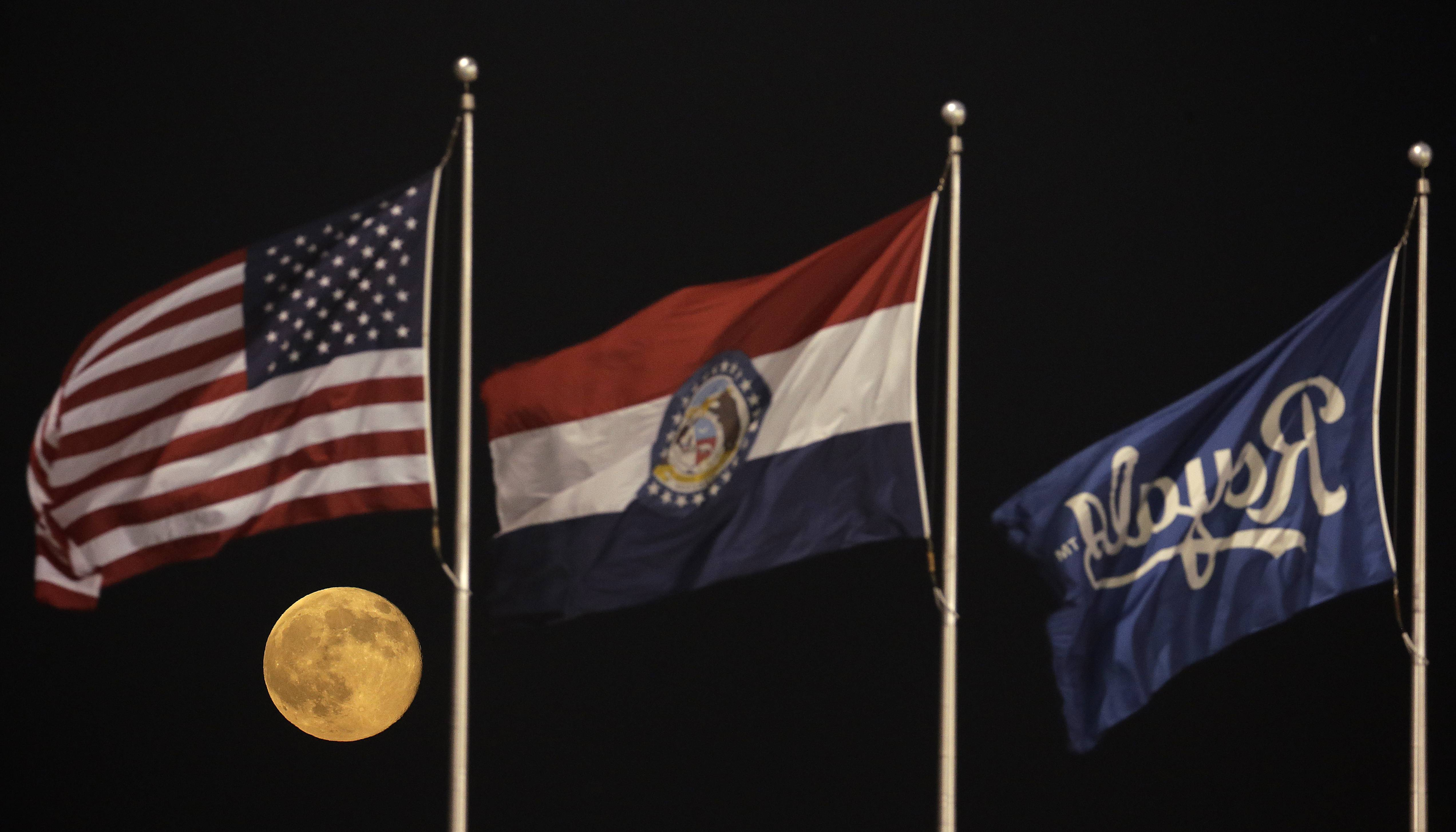 "A perigee moon, also known as a supermoon, rises beyond flags at Kauffman Stadium during a baseball game between the Kansas City Royals and the Detroit Tigers, Saturday, July 12, 2014. The phenomenon, which scientists call a ""perigee moon,"" occurs when the moon is near the horizon and appears larger and brighter than other full moons."