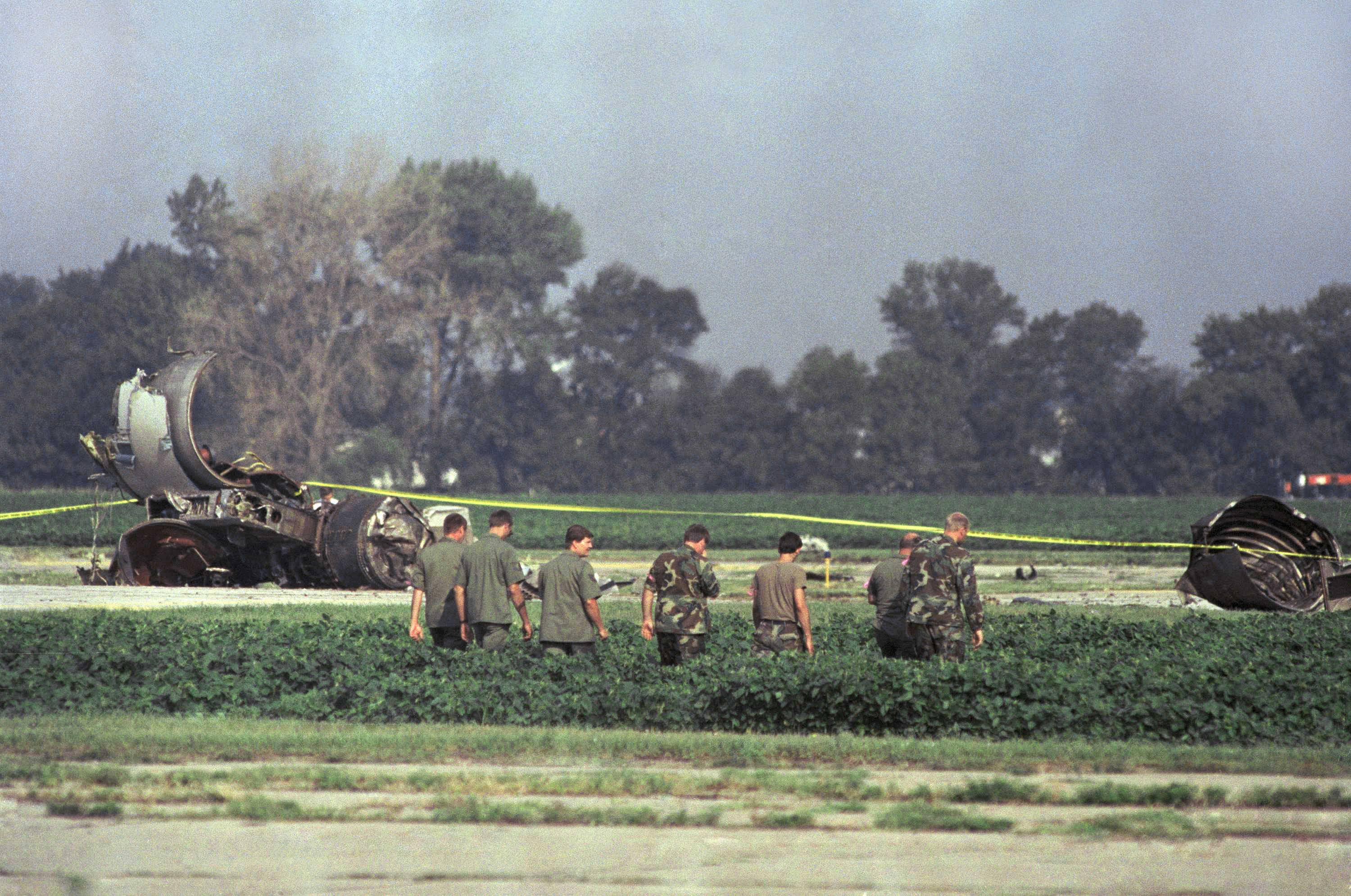 Iowa Air National Guard soldiers search a bean field near the burned engine of a United Airlines DC-10 after a crash landing at Sioux City Airport, on Wednesday, July 20, 1989, Sioux City, Iowa. The jet was en route to Chicago from Denver when it developed mechanical difficulties and tried to make an emergency landing when it crashed and burned.