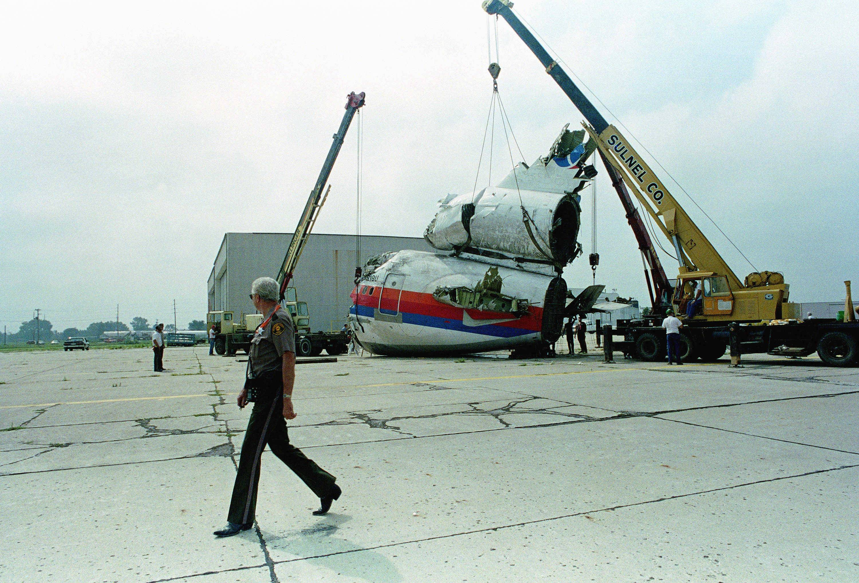 Cranes hold the tail section of the United Airlines DC-10 upright Sunday, July 23, 1989, four days after it crash landed at the Sioux City Airport in Iowa, killing 110 people. The section will later be loaded on a flatbed truck for transportation to an inspection site.