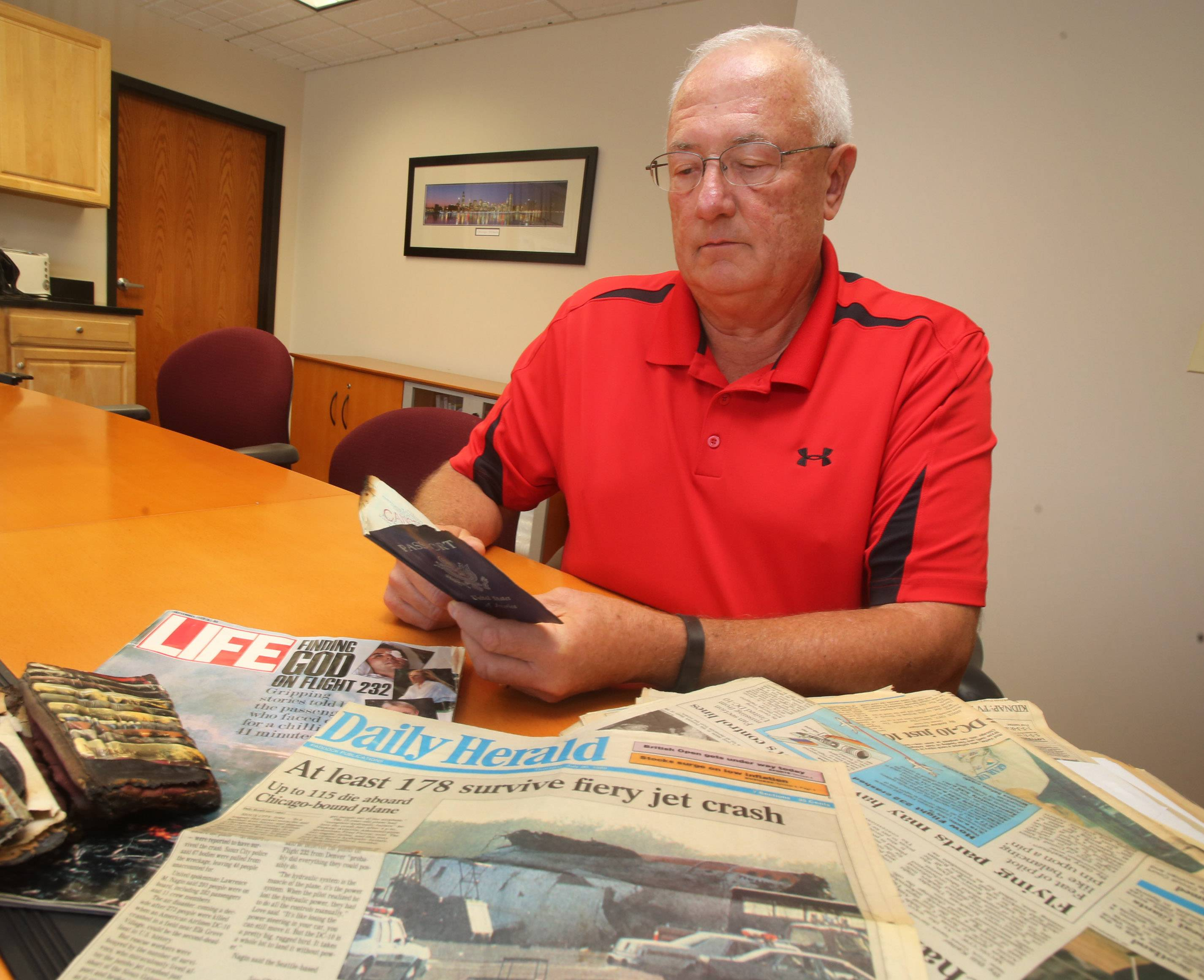 Libertyville resident Rod Vetter looks at hiis passport as he describes his experience surviving the crash of United Airlines Flight 232 on July 19, 1989 in Sioux City, Iowa.