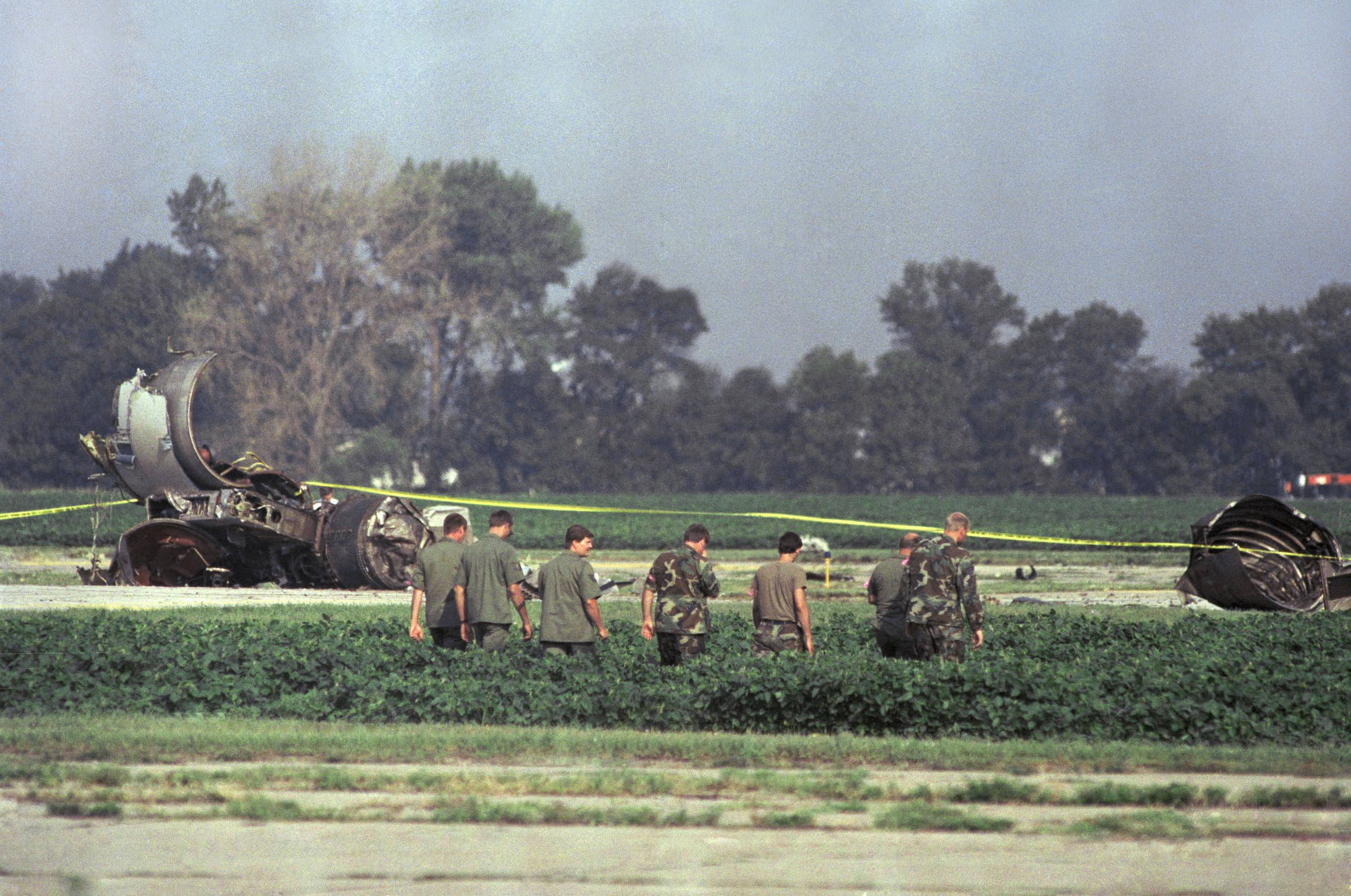 Photo shows Iowa Air National Guard soldiers search a bean field near the burned engine of a United Airlines DC-10 after a crash landing at Sioux City Airport, Wednesday, July 20, 1989, Sioux City, Iowa. The jet was enroute to Chicago from Denver when it developed mechanical difficulties and tried to make an emergency landing when it crashed and burned.