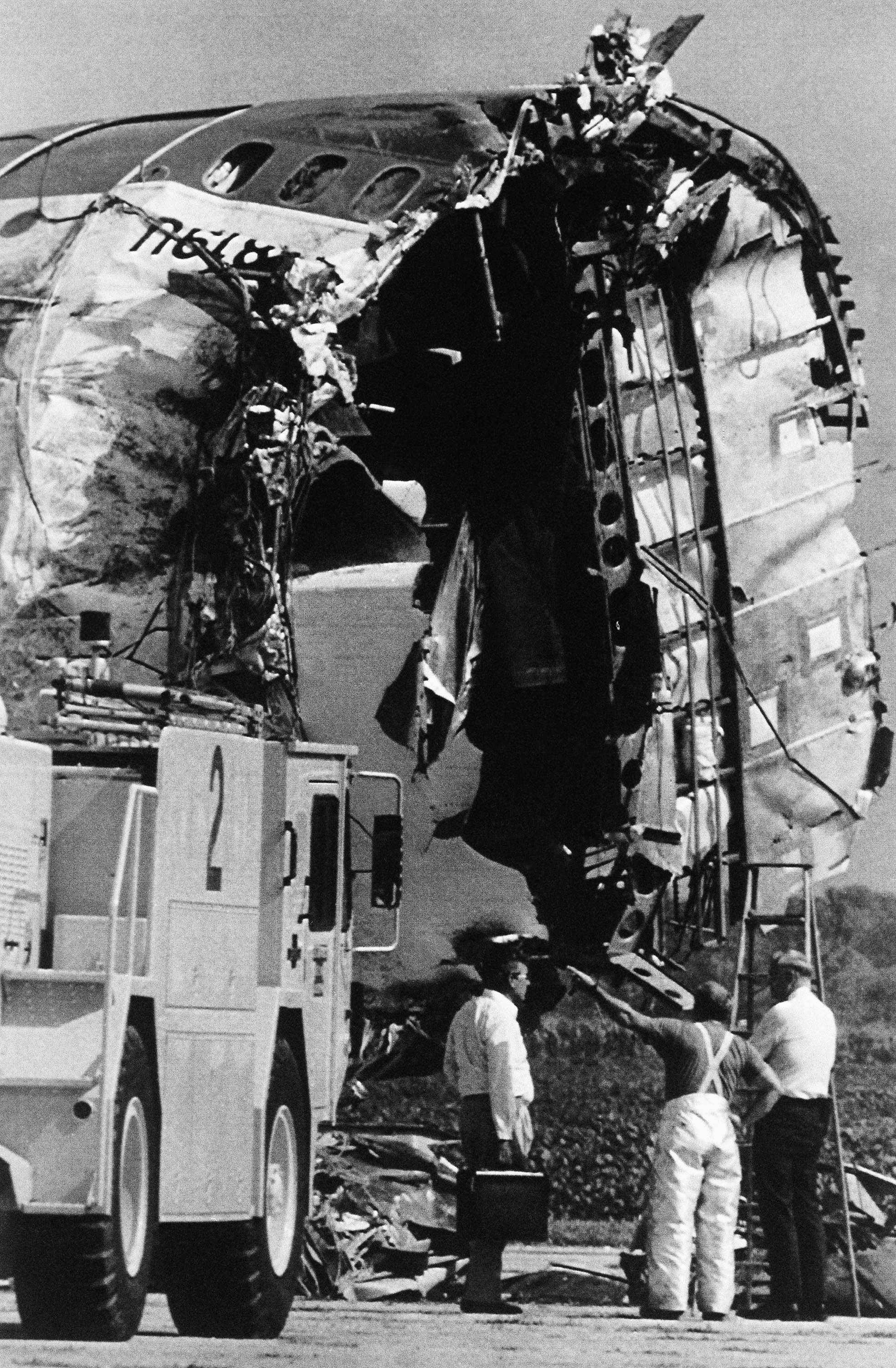 Officials look over the fuselage of United Flight 232 at the airport in Sioux City, Iowa, Monday, July 25, 1989. Fire engines were on the scene because some fuel was left in the wreckage. Later the fuselage was moved into a nearby hanger where officials could inspect it closer.