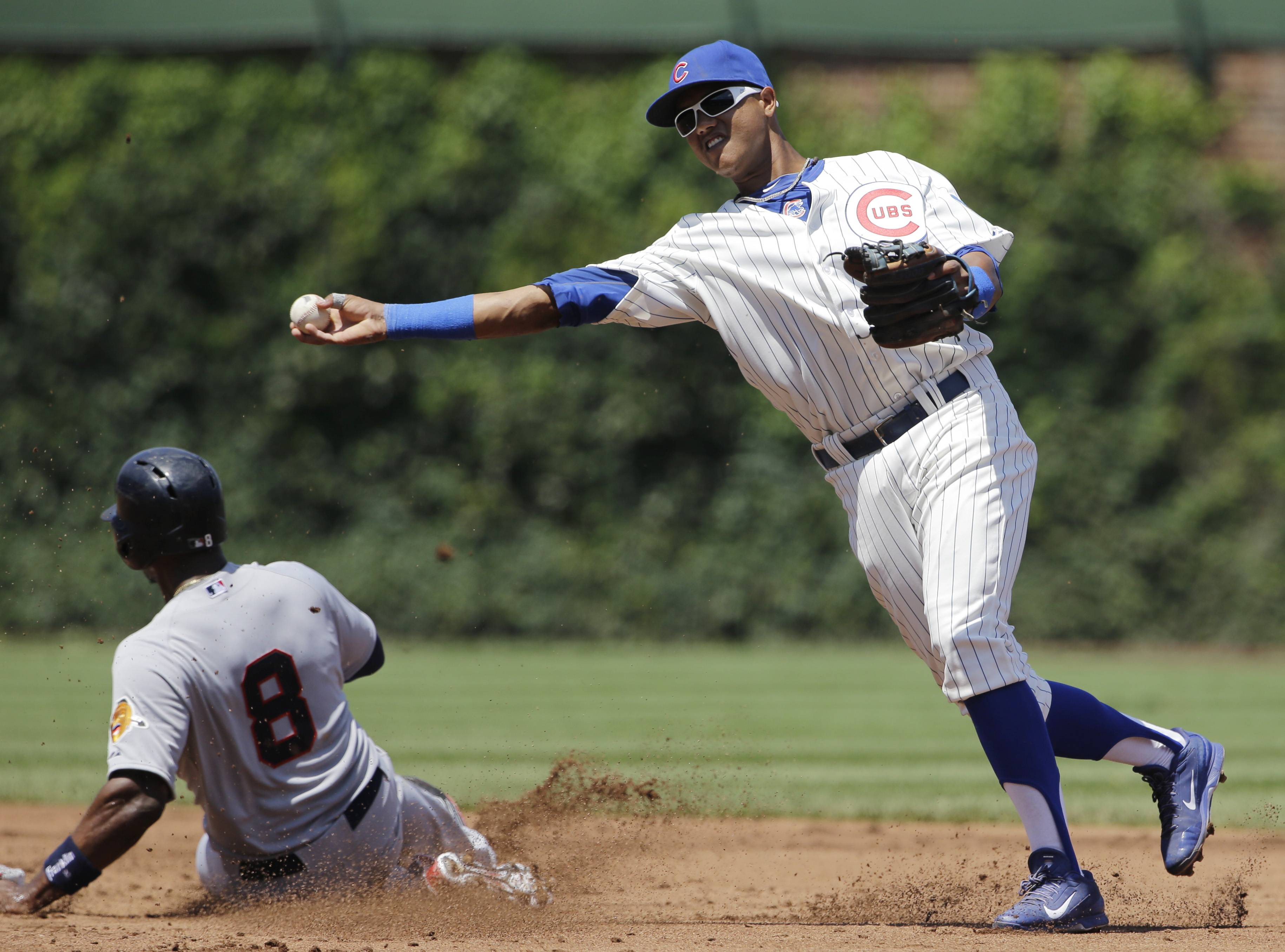 Cubs shortstop Starlin Castro, right, throws to first after forcing out Atlanta Braves Justin Upton (8) at second base during the second inning of a baseball game in Chicago, Sunday, July 13, 2014. Jason Heyward was safe at first base.