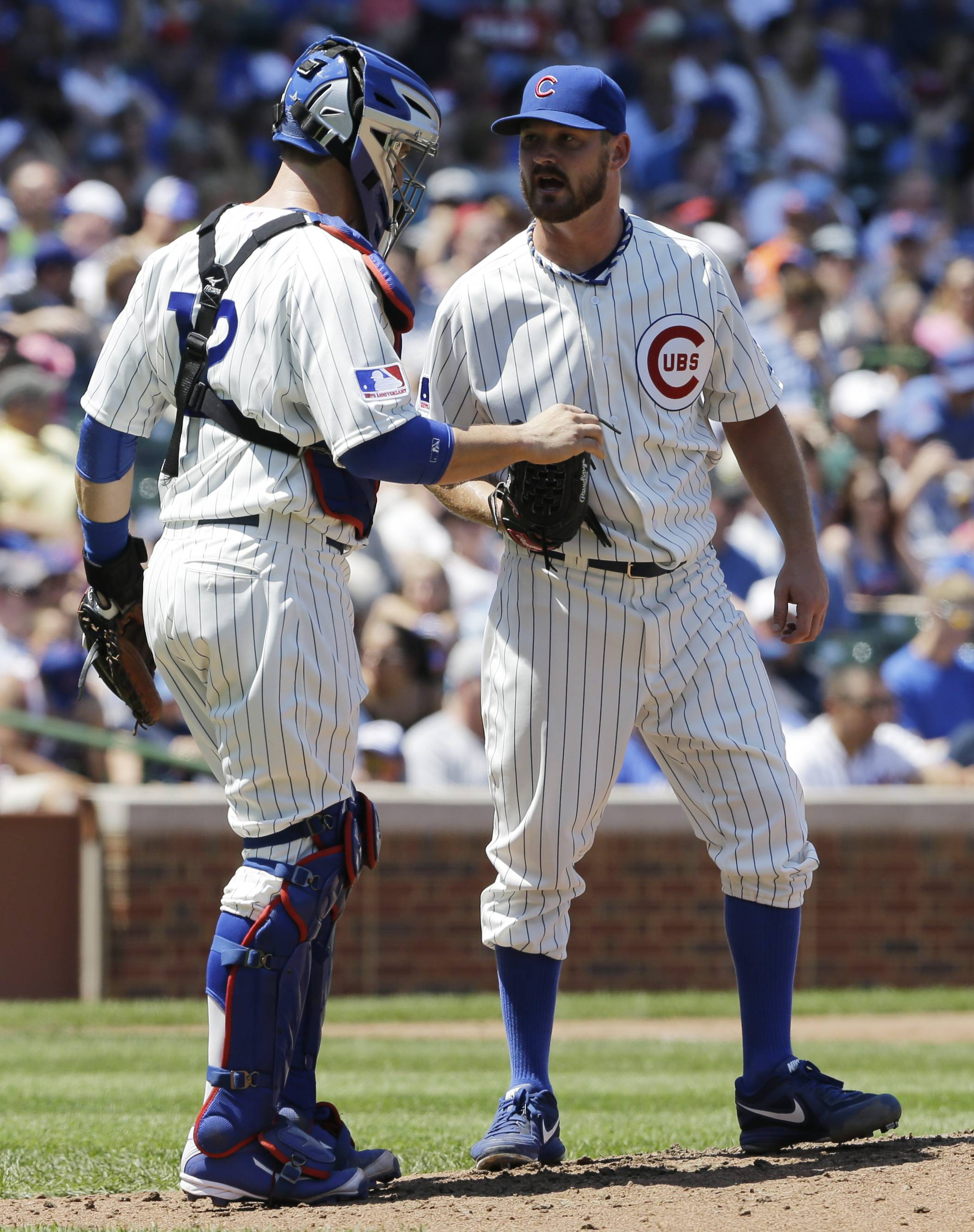 Chicago Cubs starter Travis Wood, right, talks with catcher John Baker during the third inning of a baseball game against the Atlanta Braves in Chicago, Sunday, July 13, 2014.