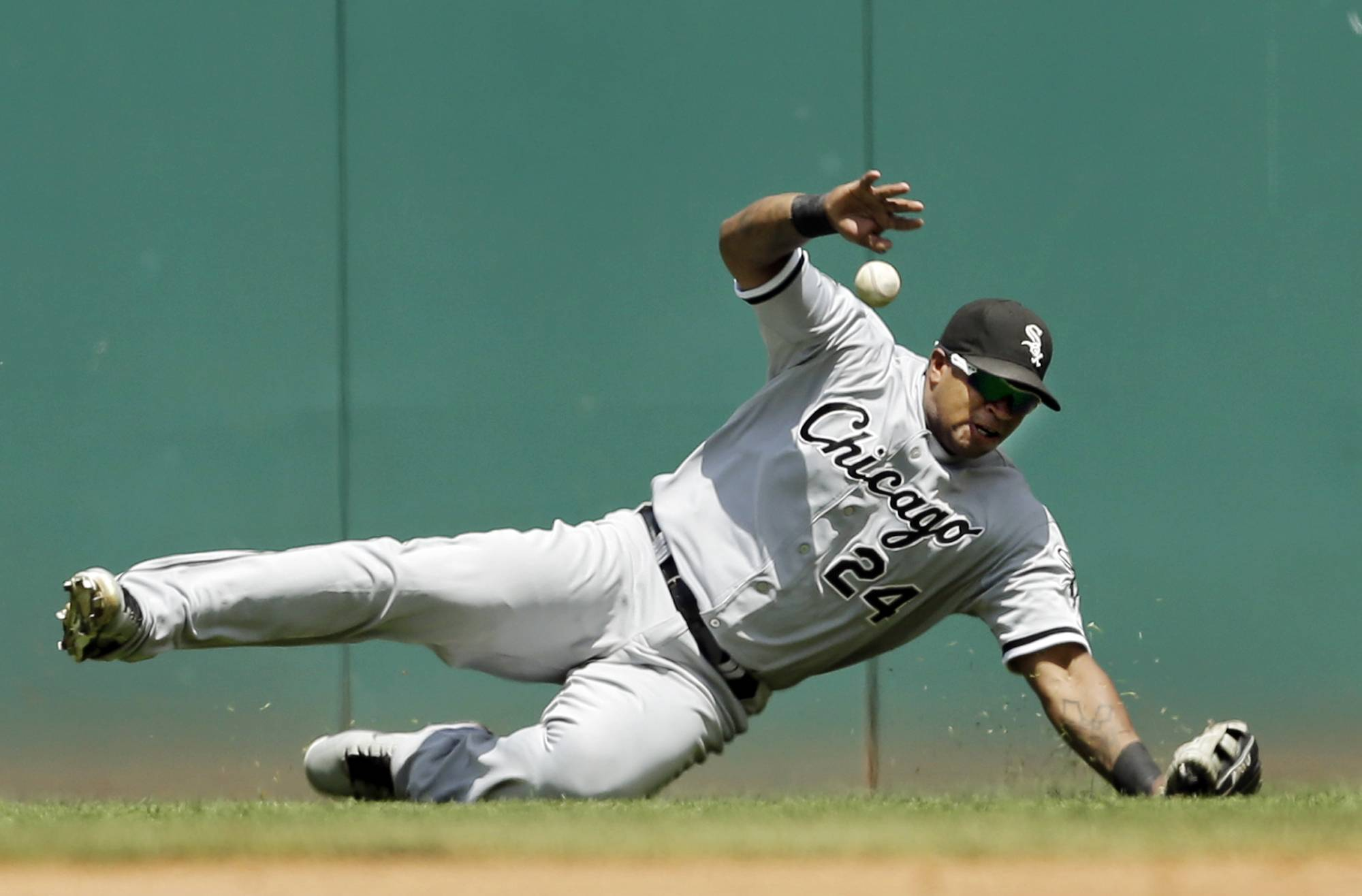 Chicago White Sox right fielder Dayan Viciedo dives for, but can't catch a line drive by Cleveland Indians' Mike Aviles that went for a double in the fourth inning of a baseball game Sunday, July 13, 2014, in Cleveland.