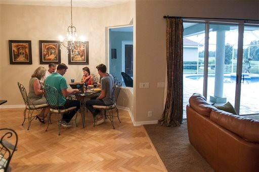 "The Muellers eat dinner in the home they live in as home managers for Showhomes in Tampa, Fla. on Tuesday, July 1, 2014. Showhomes' ""home managers"" are an elite crew of middle-class nomads tasked with keeping the luxury homes they live in immaculate to the point of not looking lived-in at all. It is, as company executives called it, ""a very different, very difficult life."""