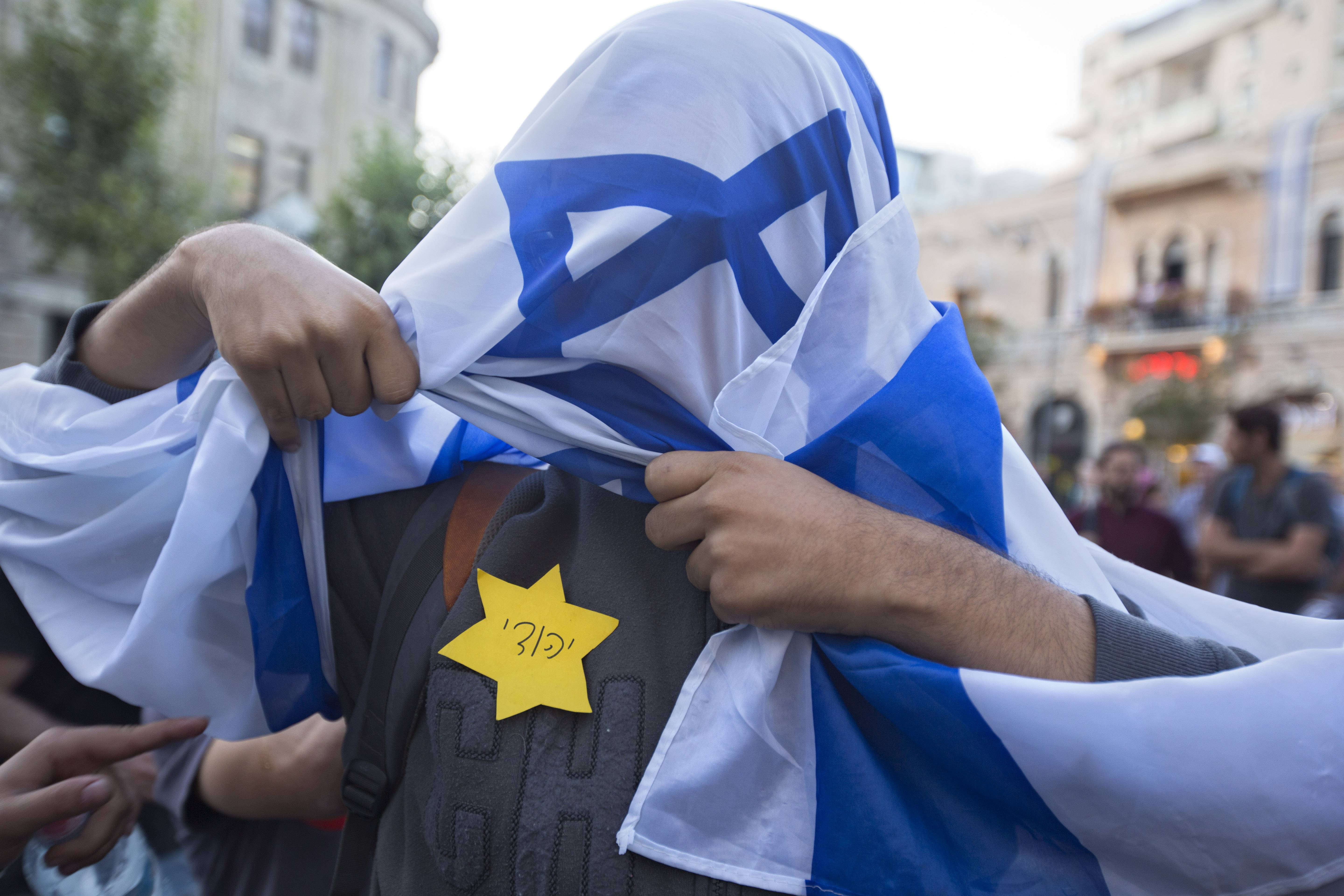 "A right-wing Israeli wears a Star of David patch with the writing ""Jew"" in Hebrew, resembling the one Jews were forced to wear in Nazi Germany as he is wrapped in an Israeli flag during a demonstration in Jerusalem Monday. The demonstrators chanted ""Israel for the Jews"" in support of the Israeli military action in the Gaza Strip."