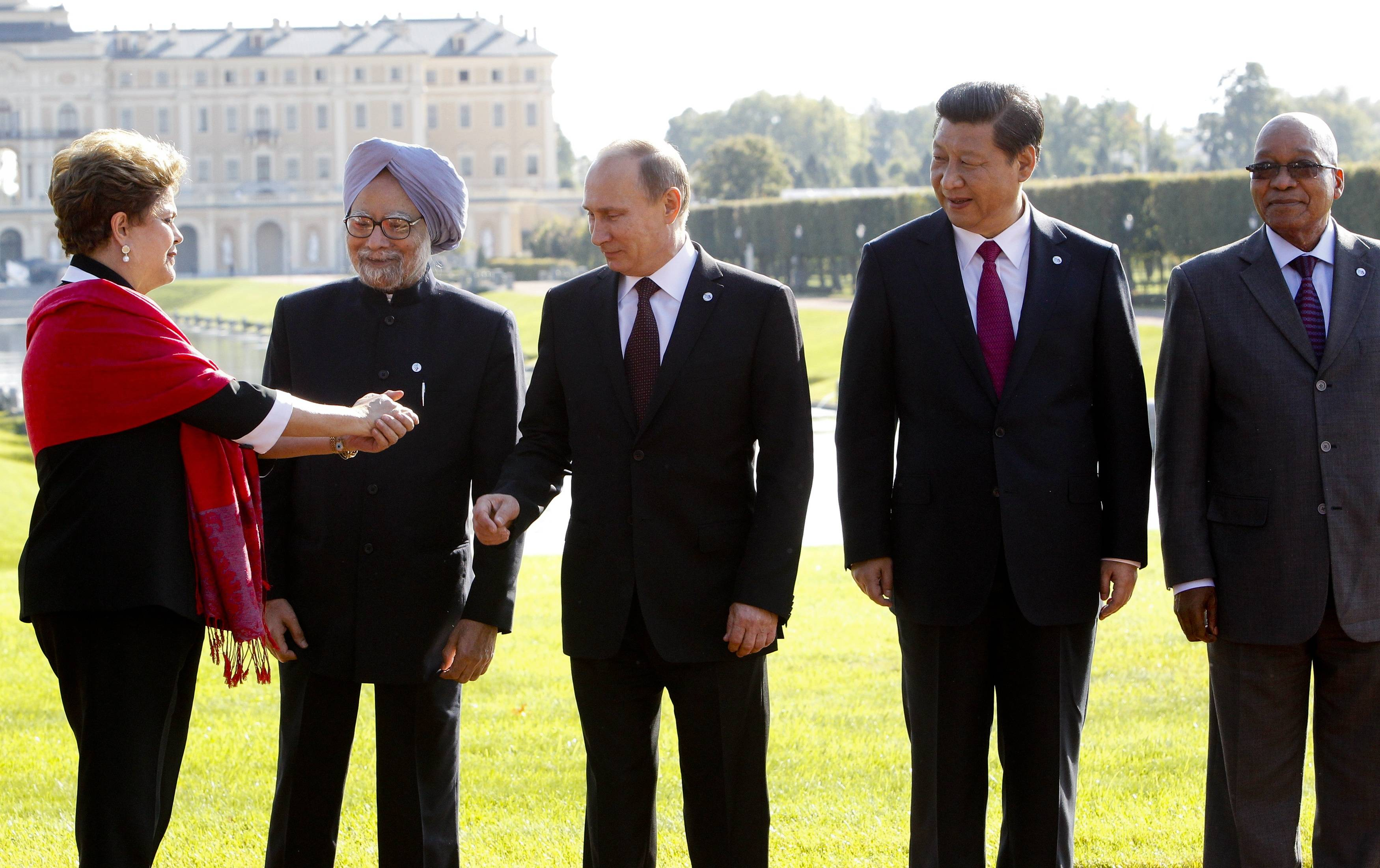 From left, Brazil's President Dilma Rousseff gestures to then Indian Prime Minister Manmohan Singh, Russia's President Vladimir Putin, China's President Xi Jinping and South African President Jacob Zuma, as they gather for a group photo after a BRICS leaders' meeting at the G-20 Summit in St. Petersburg, Russia on Sept. 5, 2013.