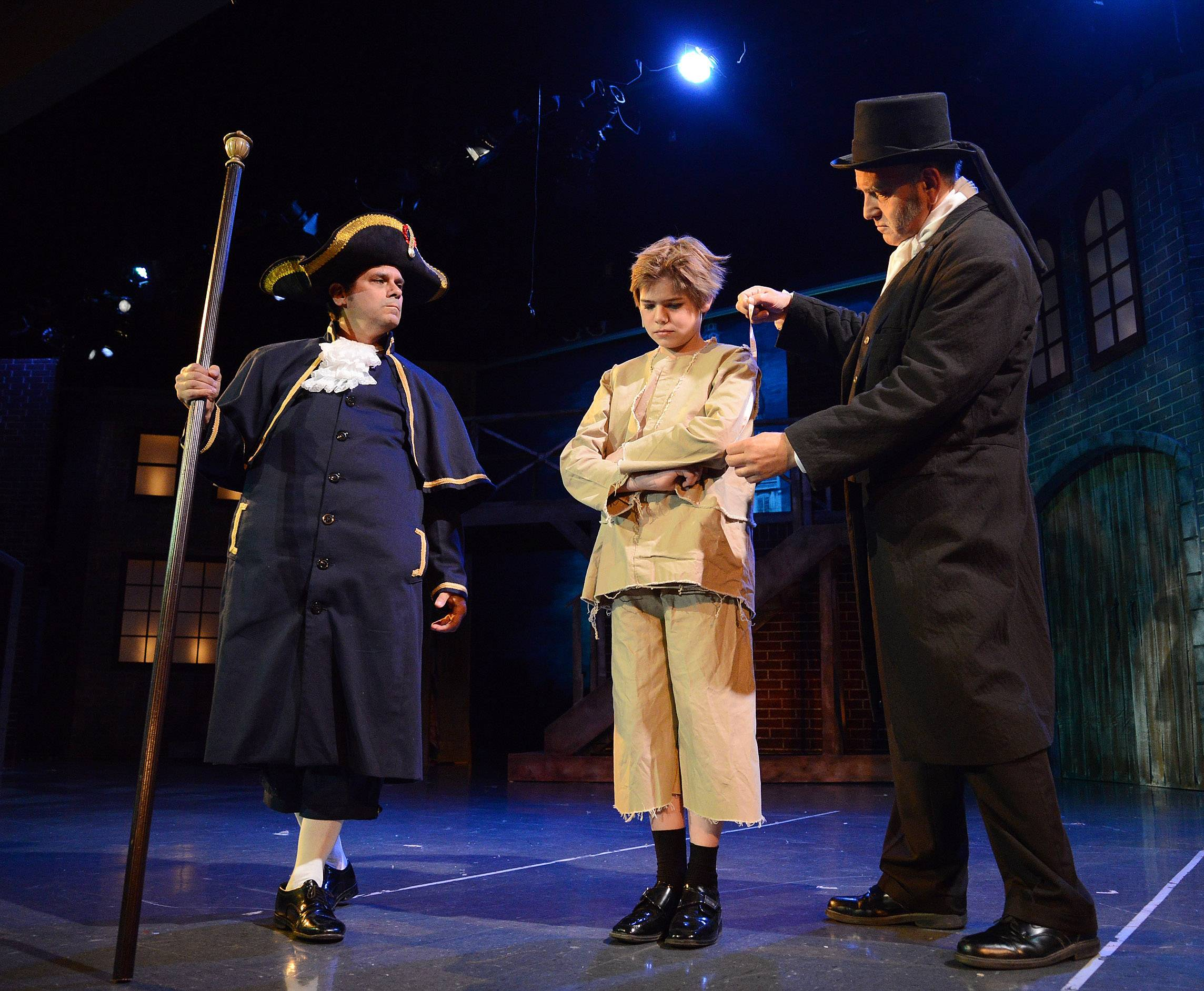"Joe Bonnadonna as Mr. Bumble, left, and Don Nowakowski as Mr. Sowerberry, size up Oliver, played by Benjamin Sanetra, in the ""That's your Funeral"" scene, during dress rehearsal."