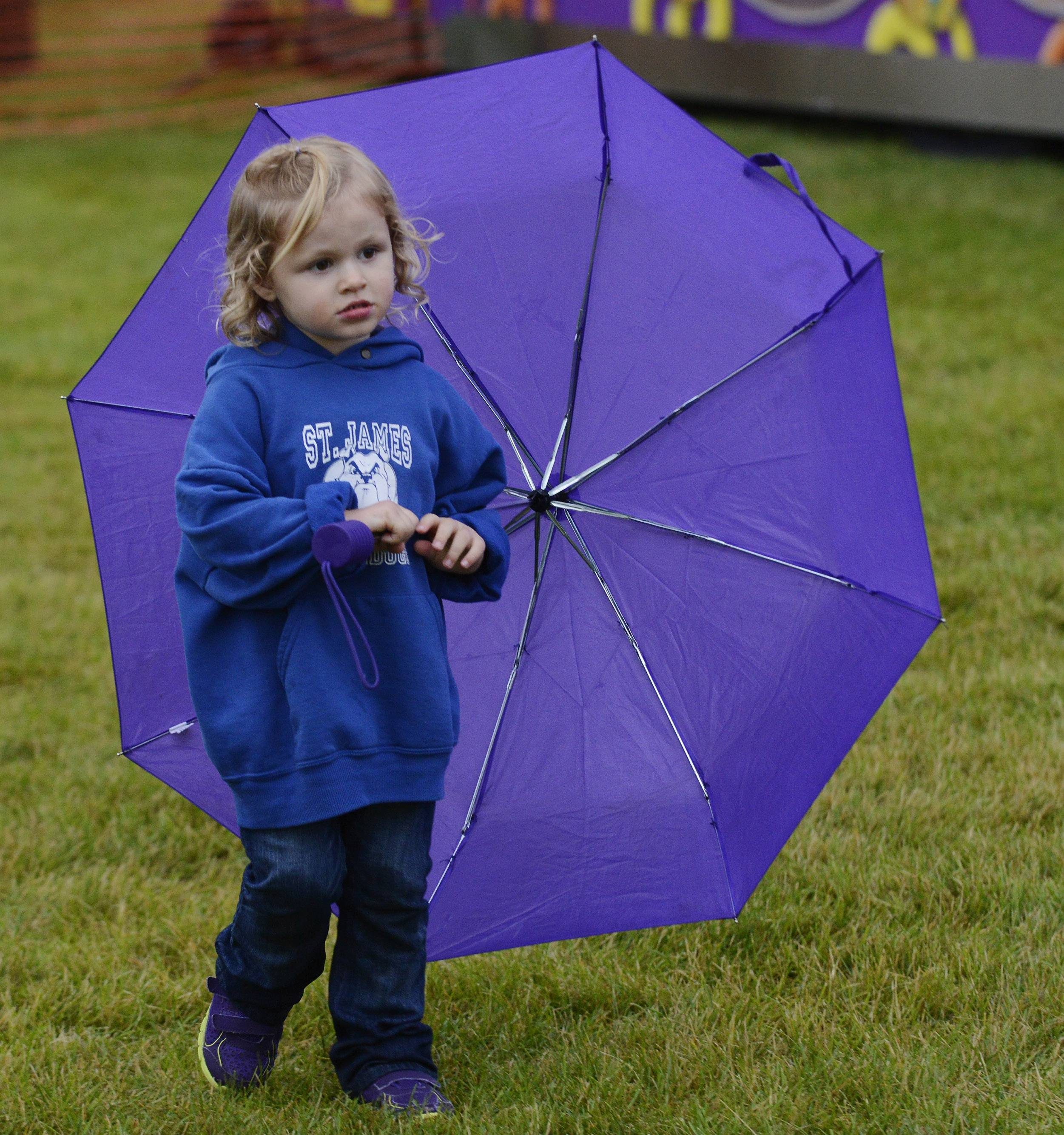 Elizabeth Flaherty, 2, of Arlington Heights, twirls an umbrella that matches her shoes as light rain falls on a 57-degree July evening on the opening night of Frontier Days in Arlington Heights.