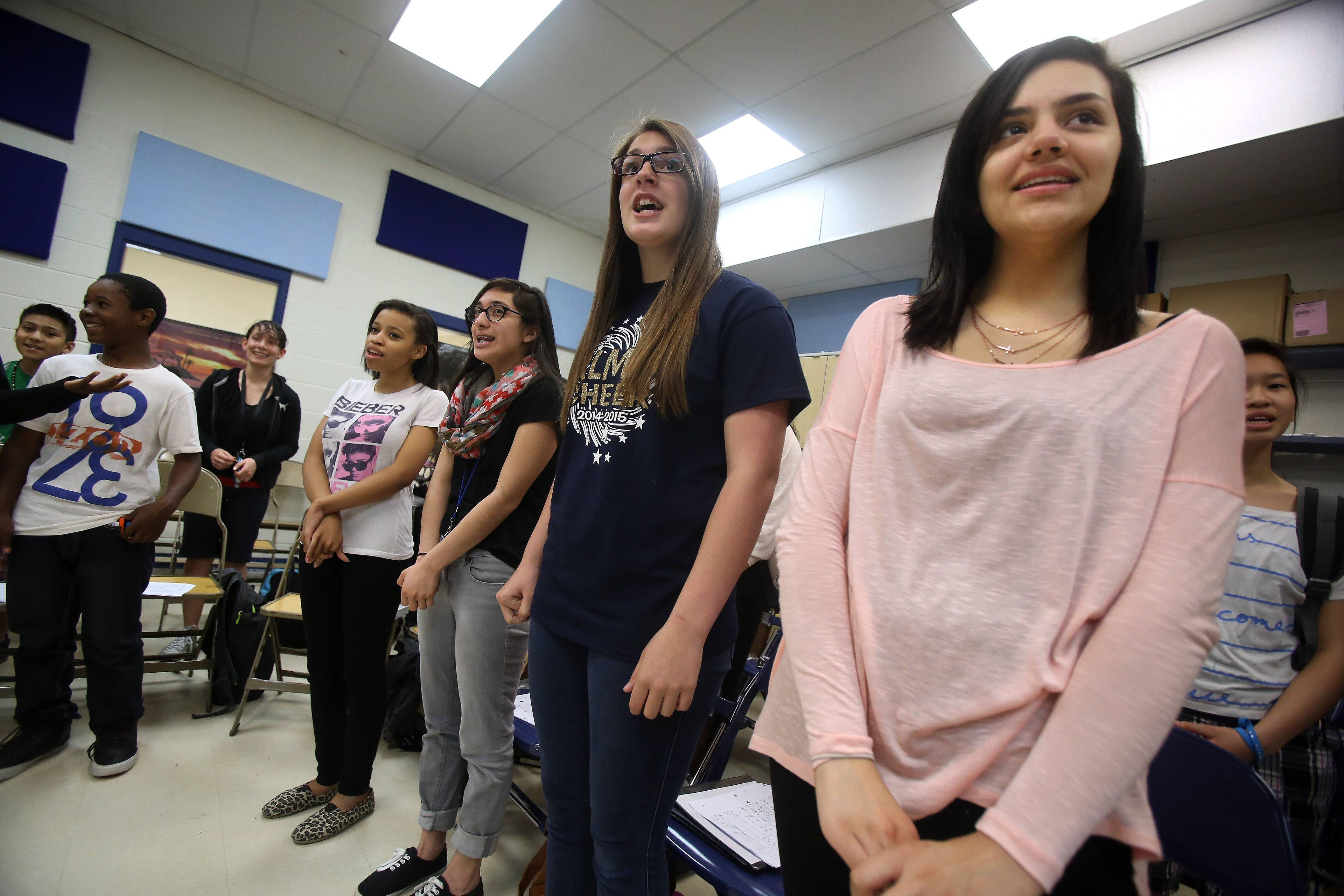 Choir students Cecilia Sanchez, right, and Hannah Jewitt sing with the rest of the children as Round Lake Middle School teacher Javier Diaz conducts.