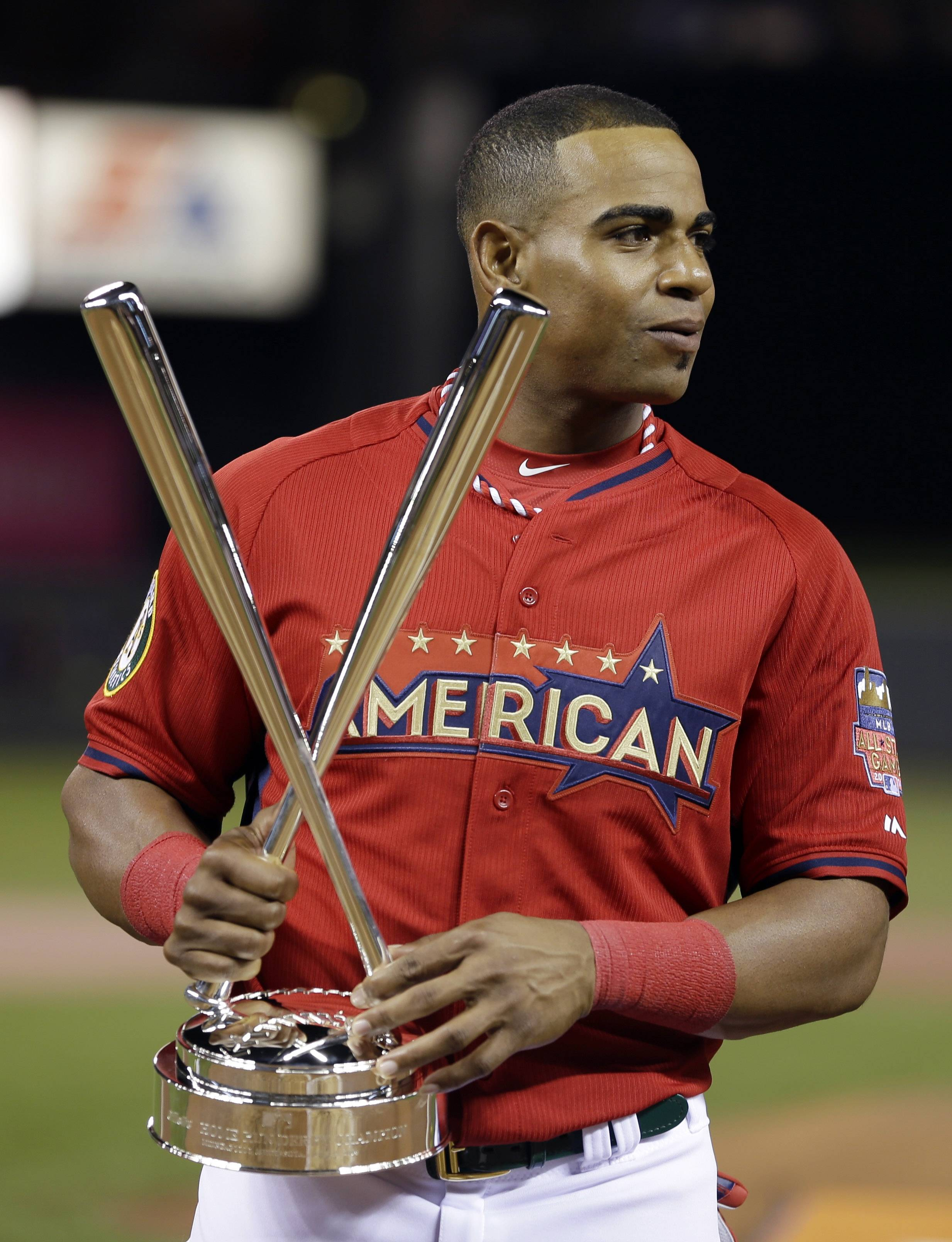 American League's Yoenis Cespedes, of the Oakland Athletics, holds the trophy after winning the MLB All-Star baseball Home Run Derby, Monday, July 14, 2014, in Minneapolis. Cespedes defeated National League's Todd Frazier, of the Cincinnati Reds, in the finals.