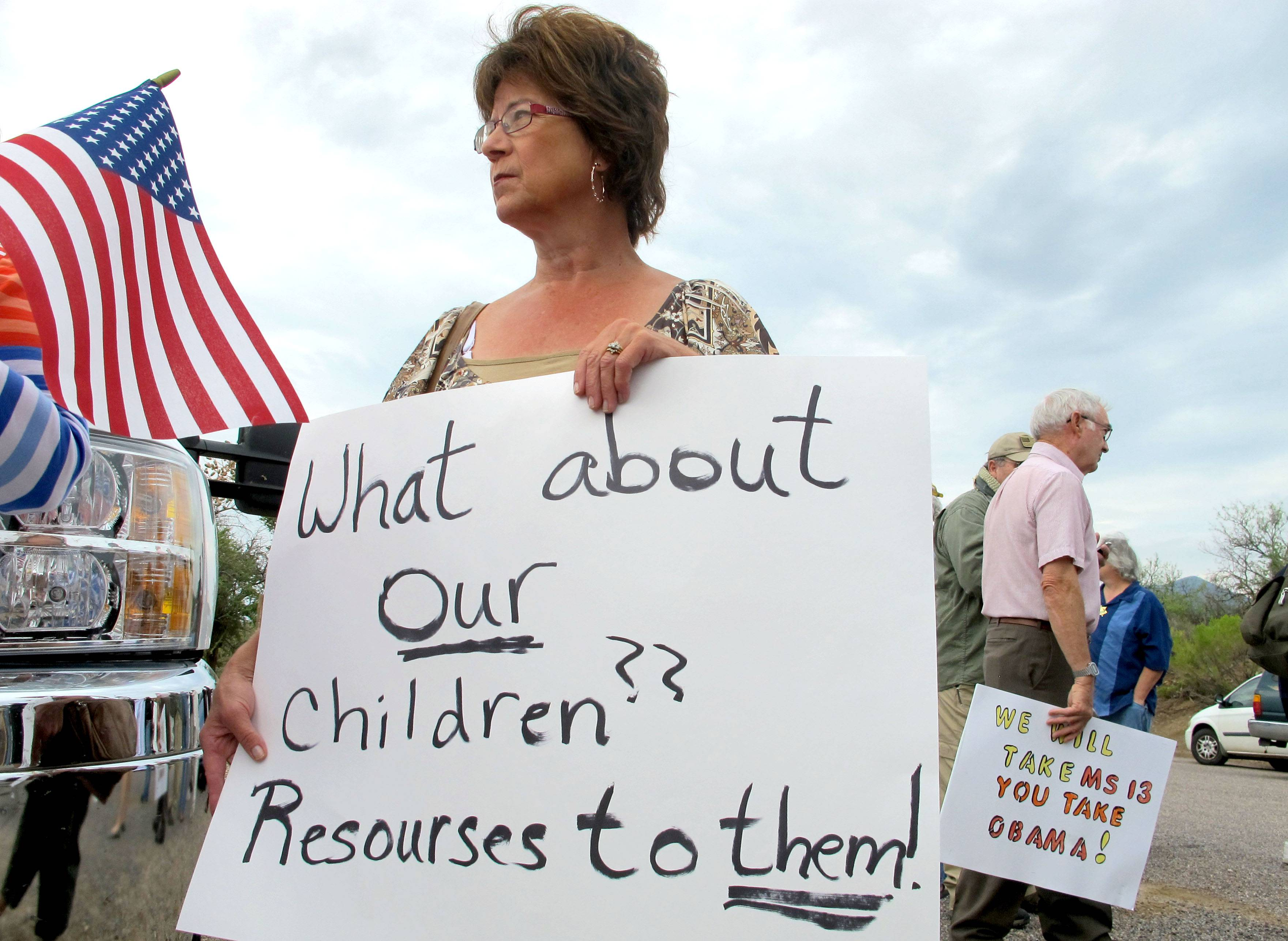 Protester Deborah Pfaff stands near the entrance to juvenile facility in an effort to stop a bus load of Central American immigrant children from being delivered to the facility Tuesday in Oracle, Ariz. Federal officials delayed the bus with no details on whether the children will arrive or not.