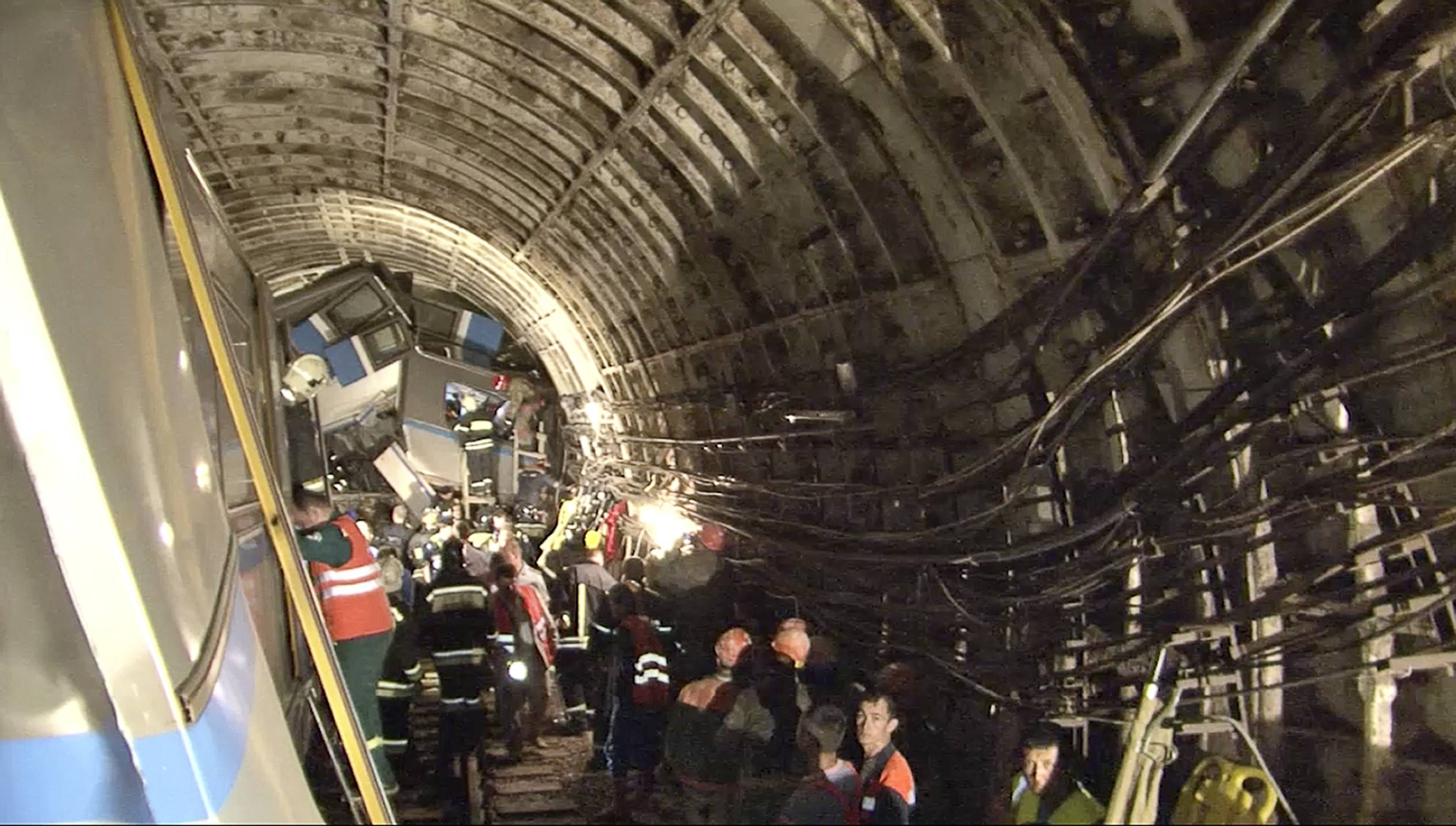 Rescue teams work inside the tunnel where several cars of a wrecked train look almost coiled, occupying the entire space of the tunnel of a Moscow subway on Tuesday.