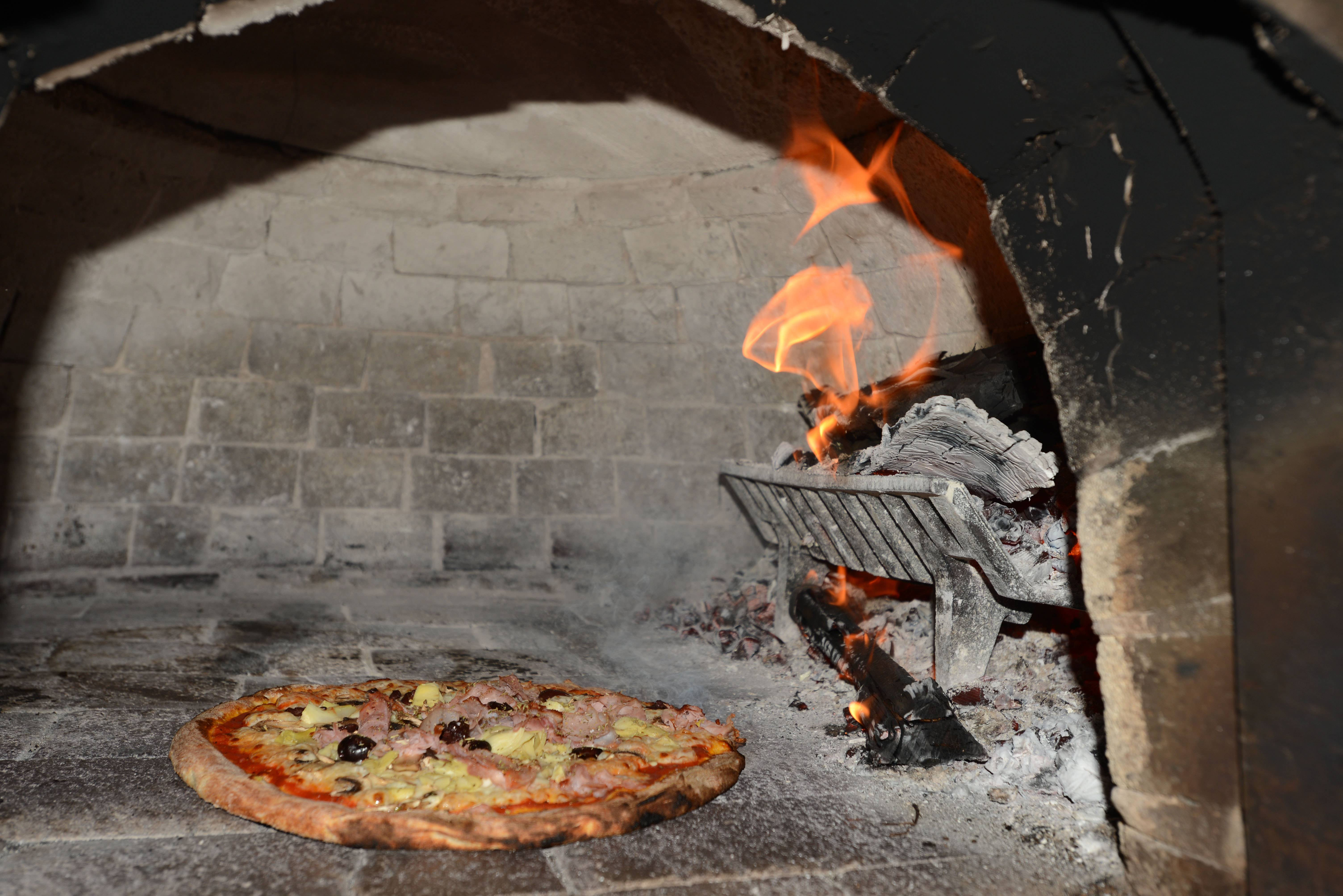 Capricciosa pizza cooks in the wood-burning oven at Elio's Pizza on Fire.