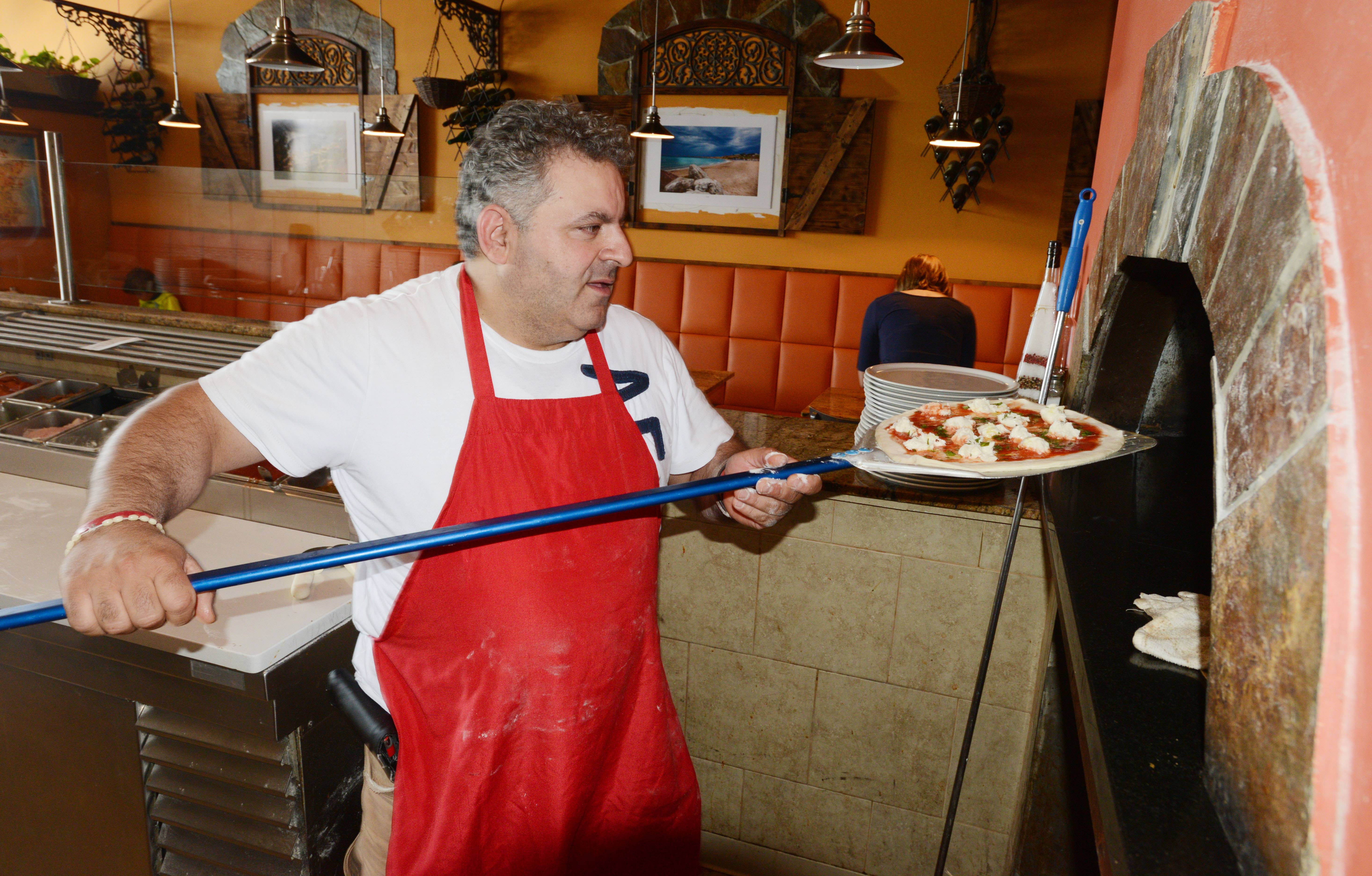 Elio Bartolotta sends a pizza into the wood-burning oven at his namesake Addison restaurant.