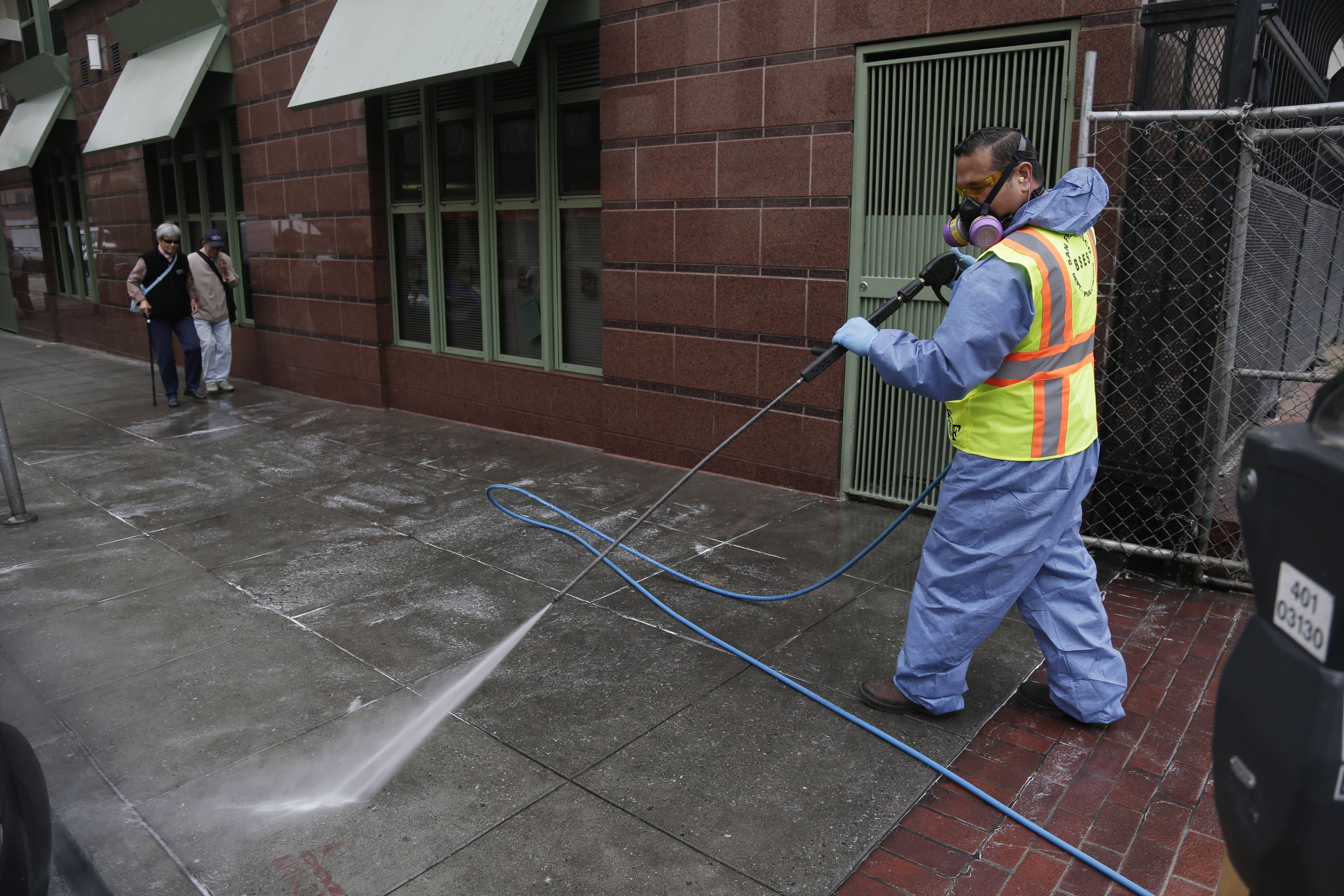 Eighi Hiastake, of the San Francisco Dept. of Public Works, washes a city sidewalk with a mixture of water and disinfectant. In one of the most drastic responses yet to California's drought, state regulators on Tuesday will consider fines of up to $500 a day for people who waste water on landscaping, fountains, washing vehicles and other outdoor uses.