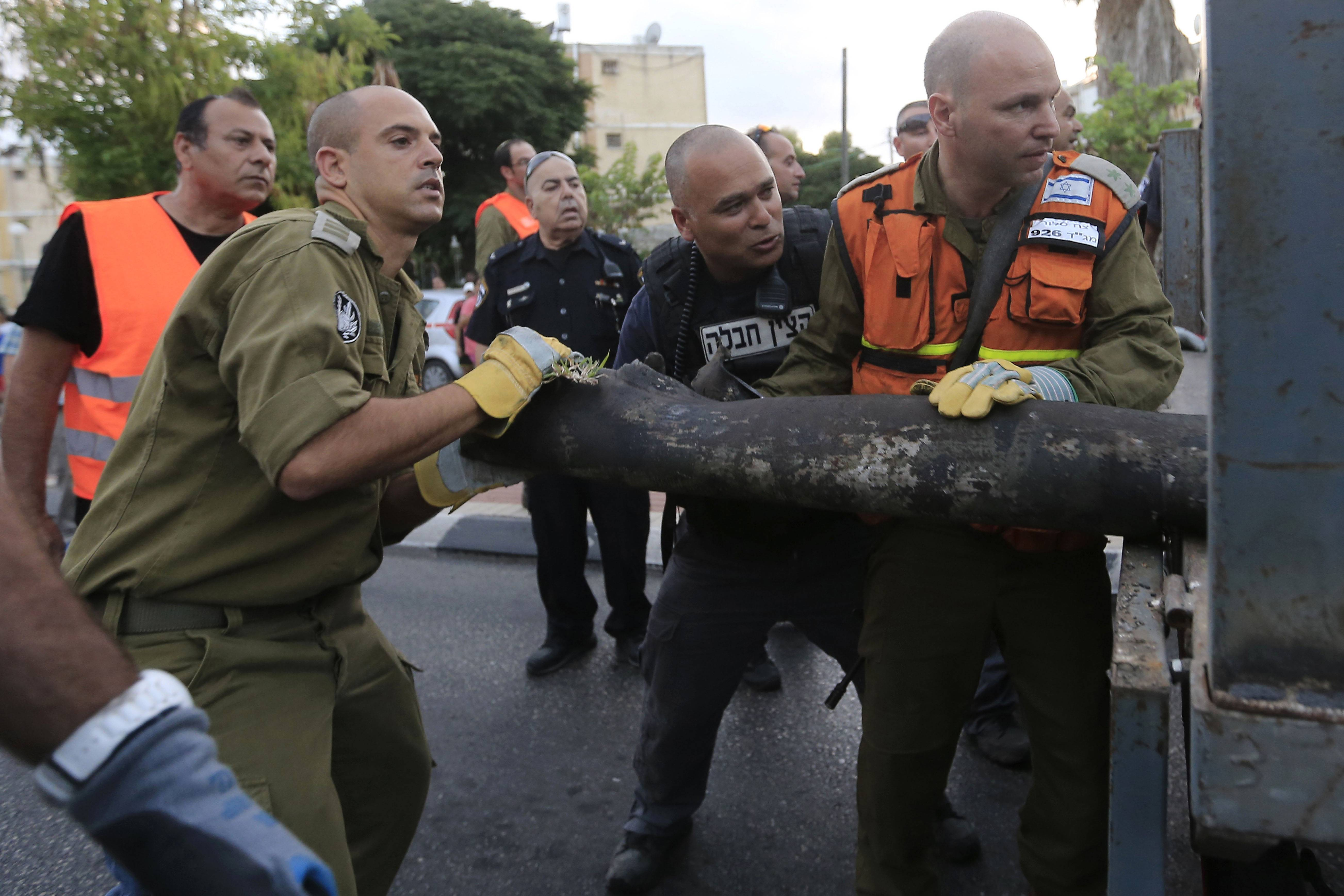 Israeli policemen and army officers carry the remains of a rocket fired from Gaza at the southern Israeli city of Ashkelon Tuesday. An Egyptian truce proposal for the conflict in Gaza unraveled Tuesday after the Islamic militant Hamas rejected the plan. Gaza militants launched scores of rockets at Israel, which after halting fire for hours finally responded with what Hamas security said were more than two dozen air strikes.