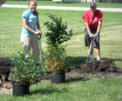 Dr. Craig Stevenson, right, of Plano, advisory council member, and staff intern Ellen Potocsnak of Naperville plant native shrubs at the Dickson-Murst Farm in Montgomery.