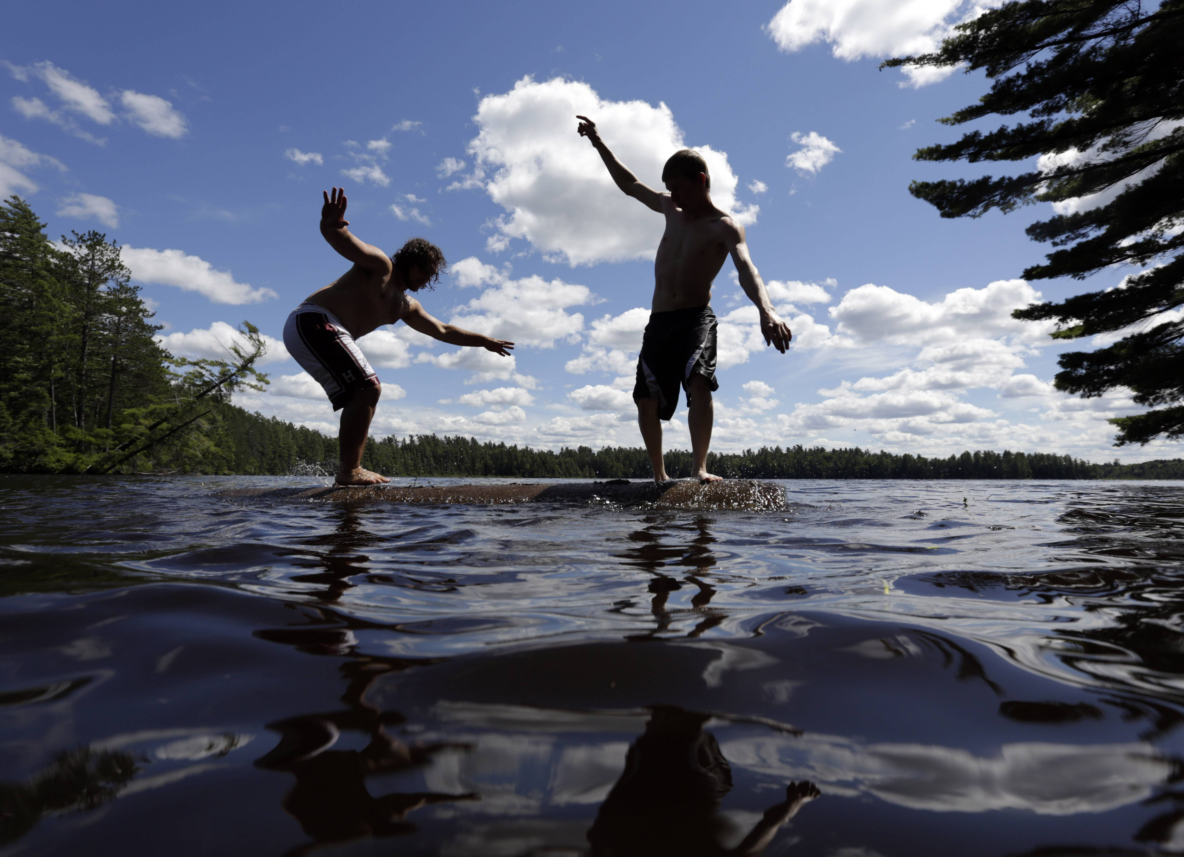 Ben Boschetto of Wayland, Mass., left, and Wes Bell of Fort Ann, N.Y., try to force each other into the water while log birling on Lower St. Regis Lake at the Adirondack Woodsmen's School at Paul Smith's College in Paul Smiths, N.Y.