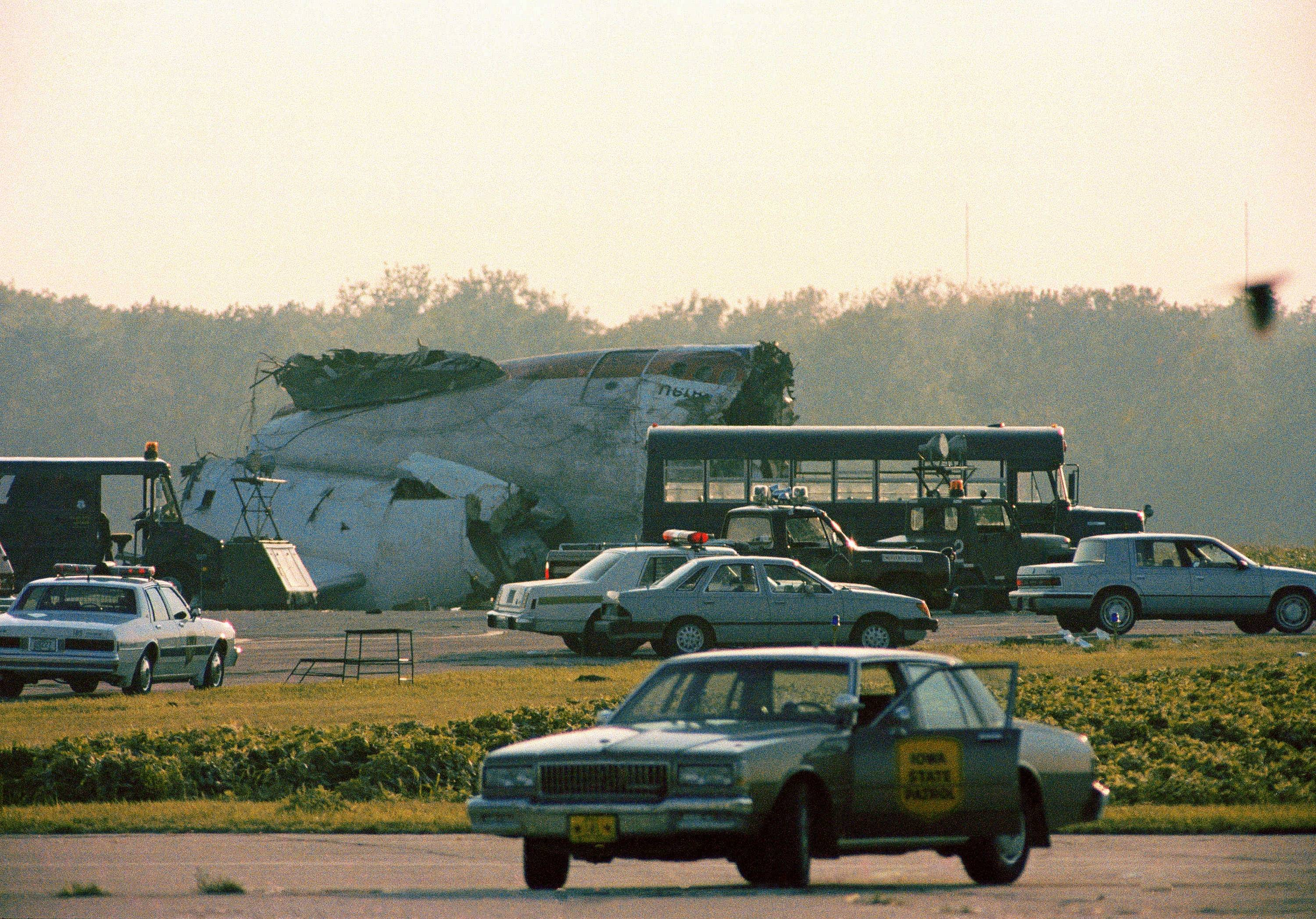 A section of the United Airlines DC-10 stands among emergency vehicles after crashing while trying to make an emergency landing in Sioux City, Iowa, July 19, 1989. The FAA acknowledges its rules fall short of what's safest for young fliers in such a catastrophe.