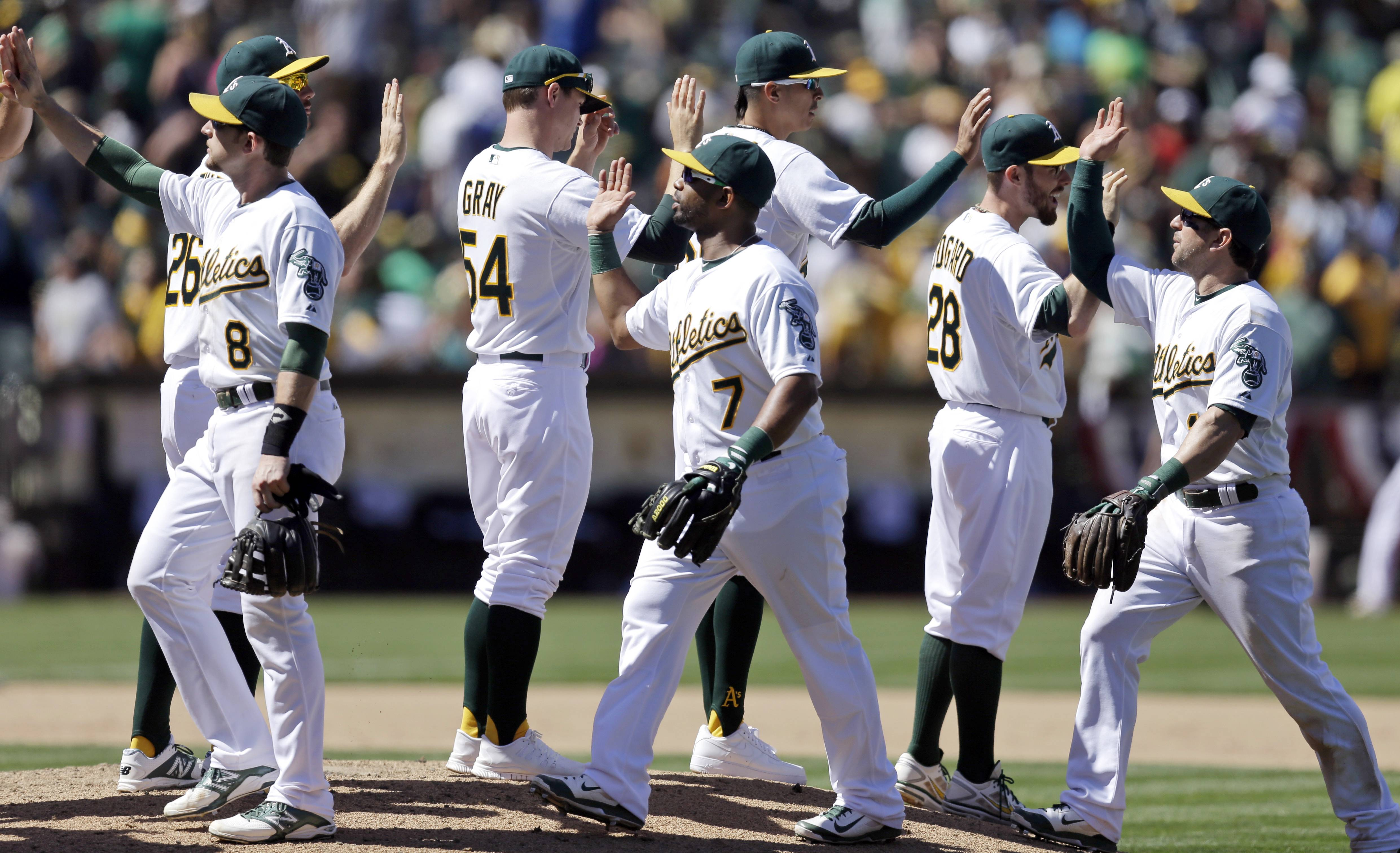 FILE - In this July 6, 2014, file photo, Oakland Athletics players including Jed Lowrie (8), Sonny Gray (54) and Alberto Callaspo (7) celebrate their four game sweep of the Toronto Blue Jays after a baseball game in Oakland, Calif. The small-budget Athletics are baseball's best team at the break in a division featuring some of the highest-paid stars. The Giants are right in the chase for the NL West crown despite some recent stumbles. It's only mid-July and there is already talk of a special October and, perhaps, a Bay Bridge Series with far more significance come fall. (AP Photo/Ben Margot, File)