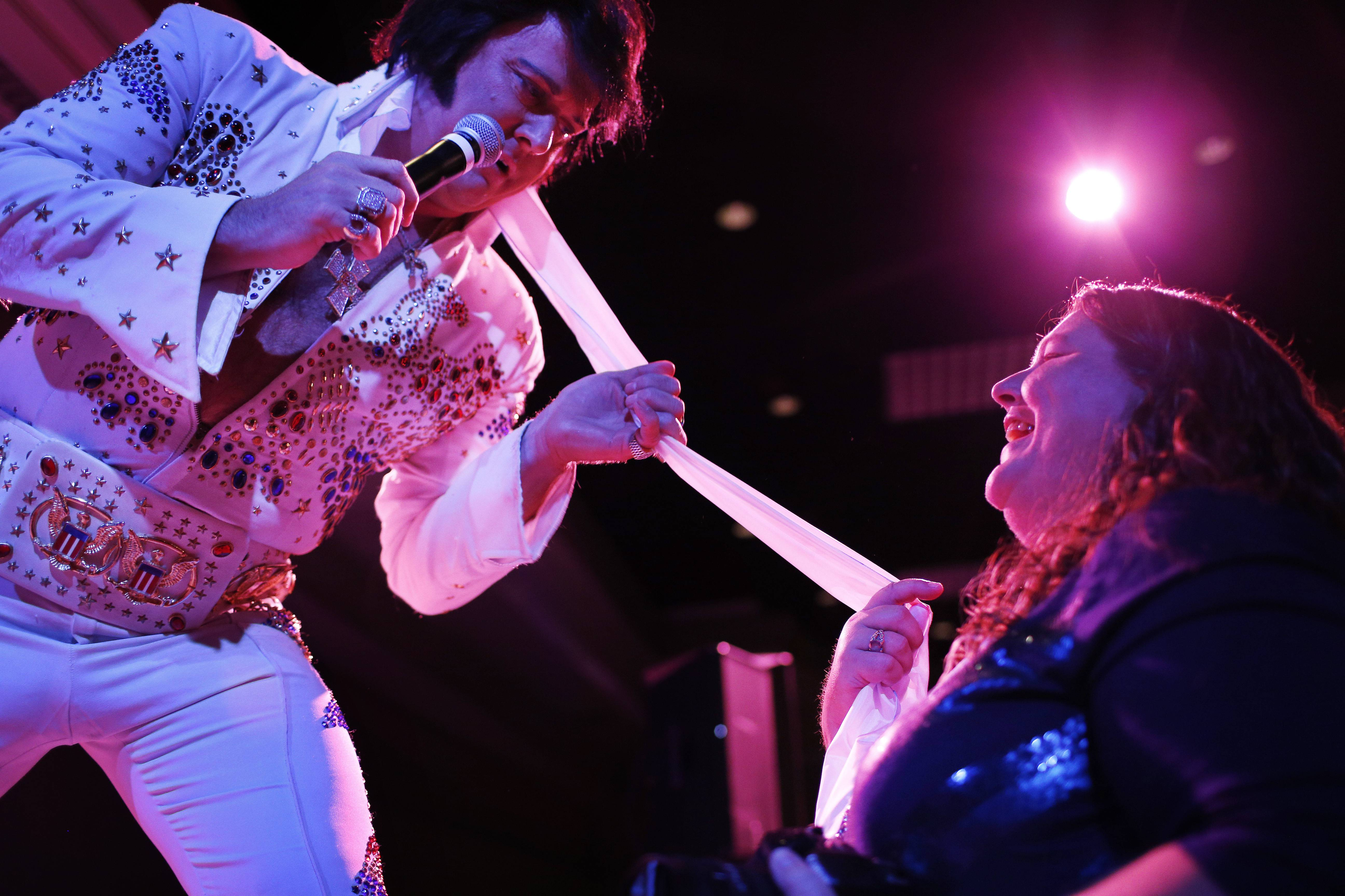 Elvis tribute artist Jim Westover, left, of Arizona City, Ariz., gives a scarf to fan Juanita Curtice, of Woodbridge, Va., during the Las Vegas Elvis Festival. Some three dozen Elvis tribute artists took their gyrating hips and curled lips to the stage over the weekend to see who could do the most convincing portrayal.