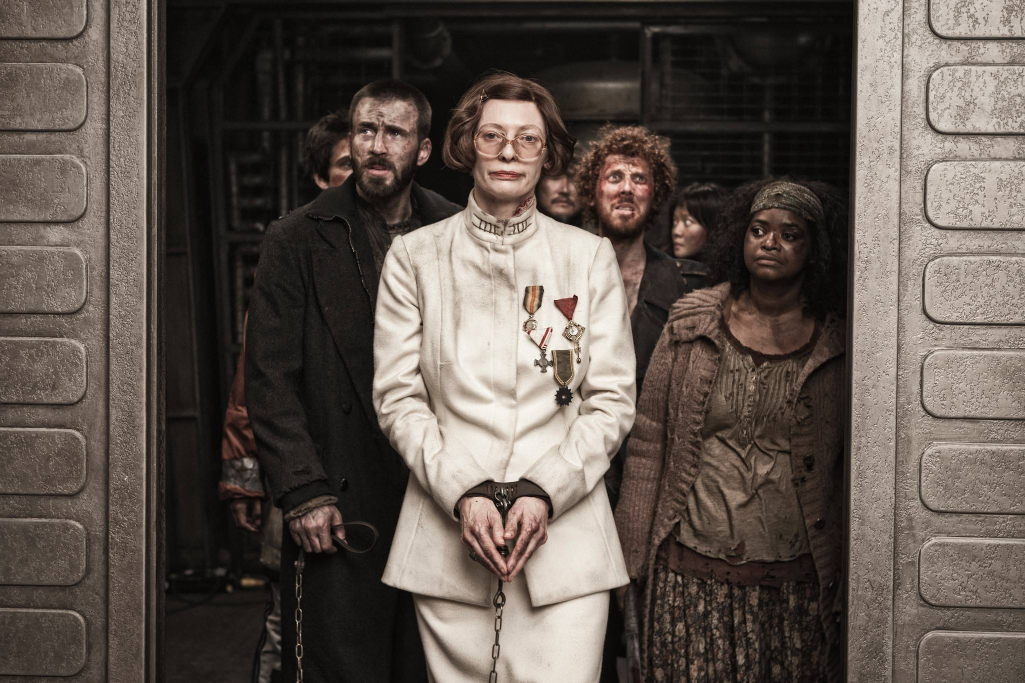 "Mason (Tilda Swinton), center, is taken prisoner by rebel leader Curtis (Chris Evans), left, and Tanya (Octavia Spencer), right, in ""Snowpiercer."""