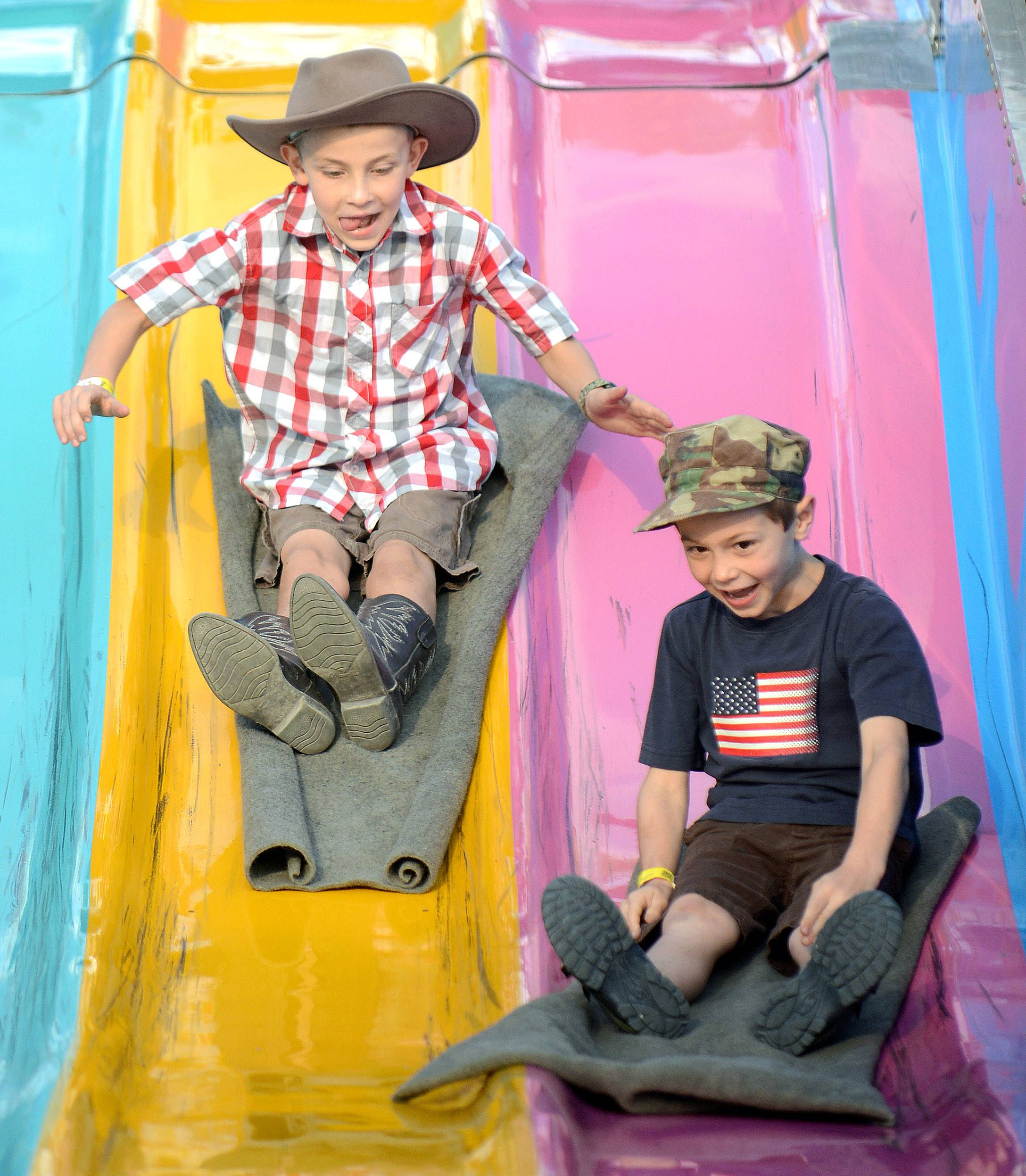 Aiden Best, 9, of Hampshire, and his brother, Jacob, 7, zip down the Fun Slide ride on the Midway Wednesday during opening day of the 146th Kane County Fair in St. Charles. Aiden showed chickens earlier in the day for the first with his 4-H club from Burlington.