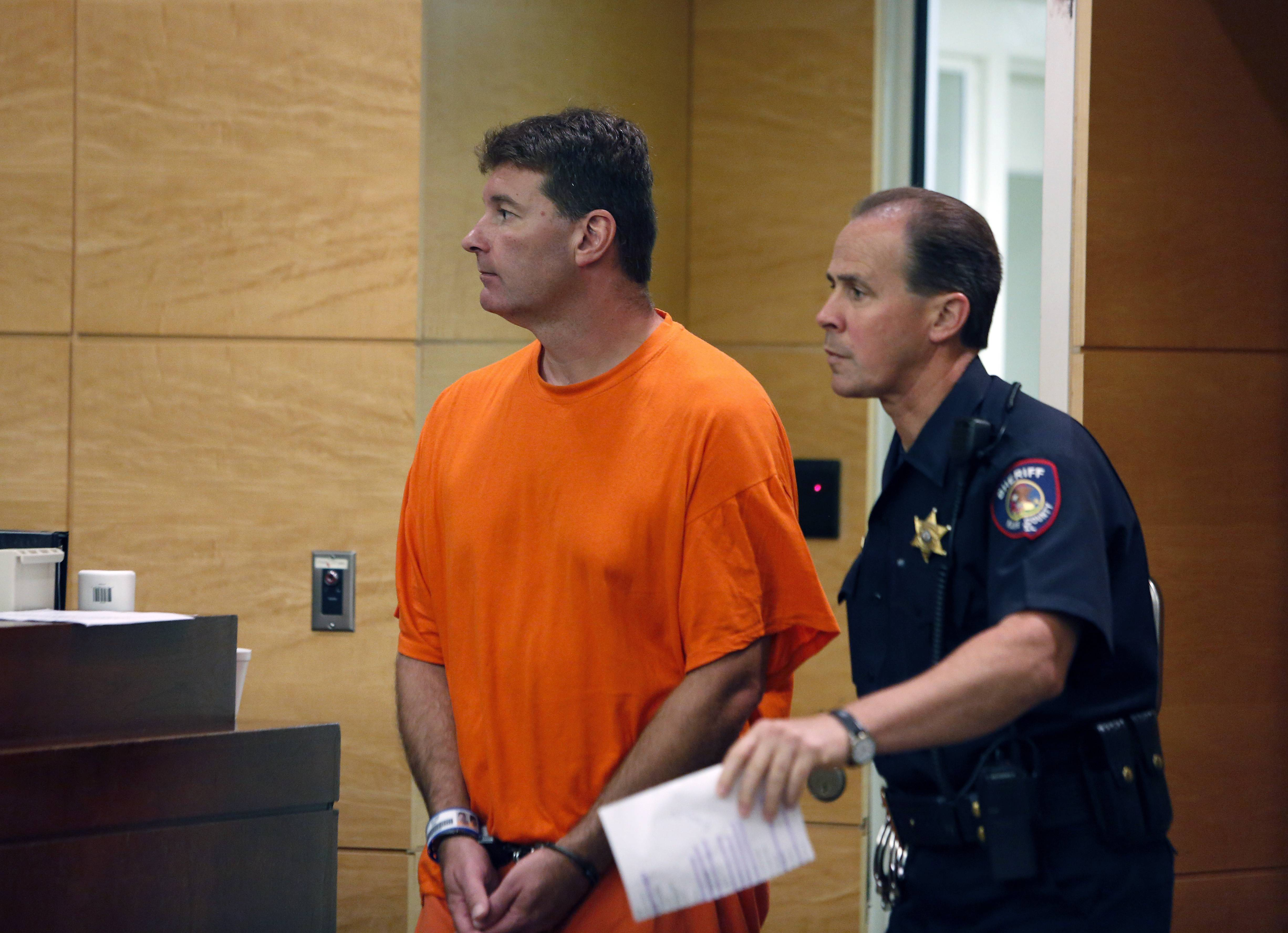 Shadwick R. King is brought into the court by Kane County Sheriff's Deputy Bob Schwer before appearing in front of Judge James C. Hallock Wednesday in St. Charles. King, 47, is accused of killing his wife, Kathleen King, 32, by asphyxiating her July 6 at their Geneva home and dumping her body along railroad tracks near their home, authorities said.