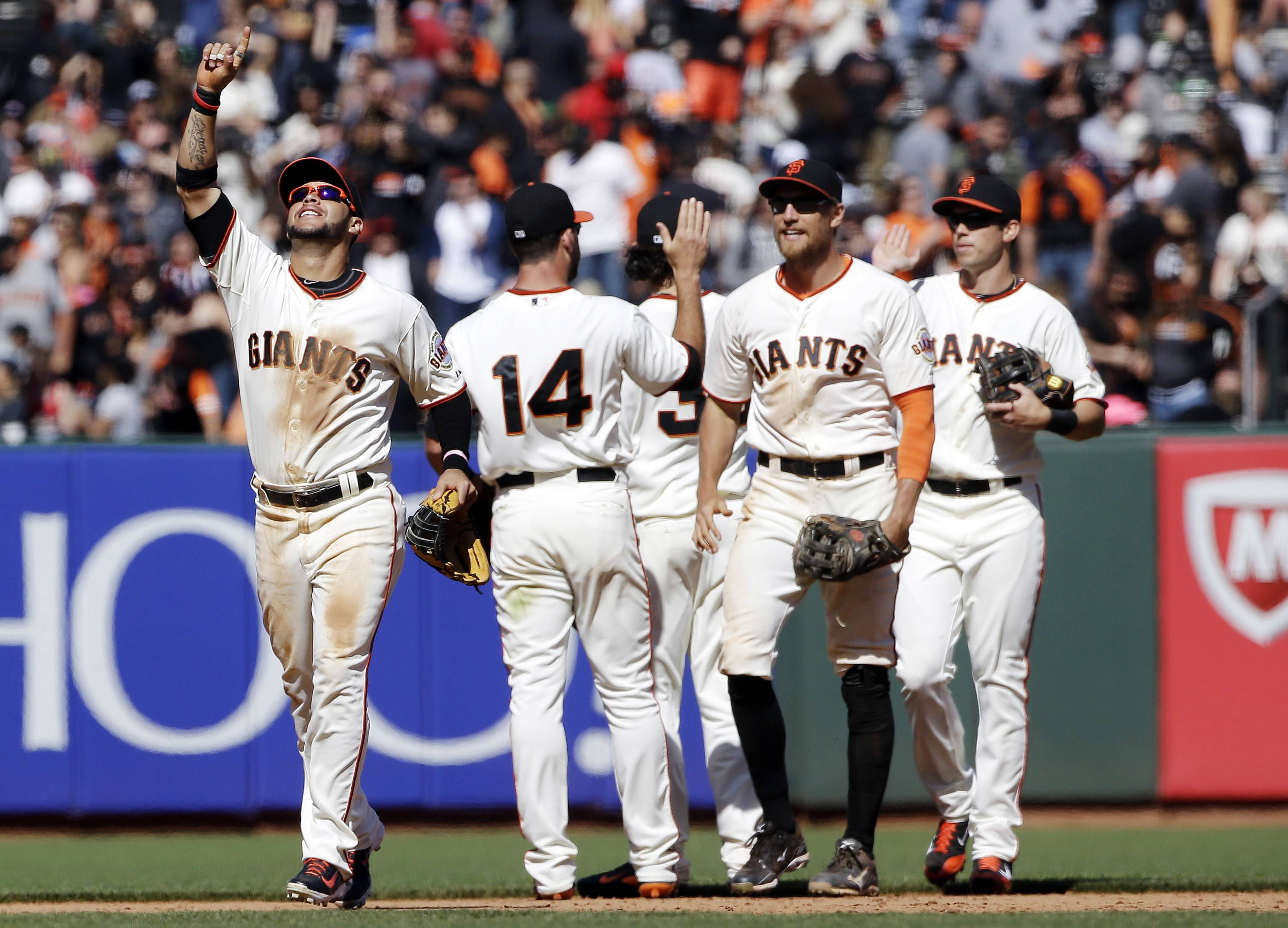 FILE - In this May 18, 2014, file photo, from left, San Francisco Giants' Gregor Blanco, Brandon Hicks (14), Hunter Pence and Tyler Colvin celebrate a 4-1 win over the Miami Marlins in a baseball game in San Francisco. The small-budget Athletics are baseball's best team at the break in a division featuring some of the highest-paid stars. The Giants are right in the chase for the NL West crown despite some recent stumbles. It's only mid-July and there is already talk of a special October and, perhaps, a Bay Bridge Series with far more significance come fall.