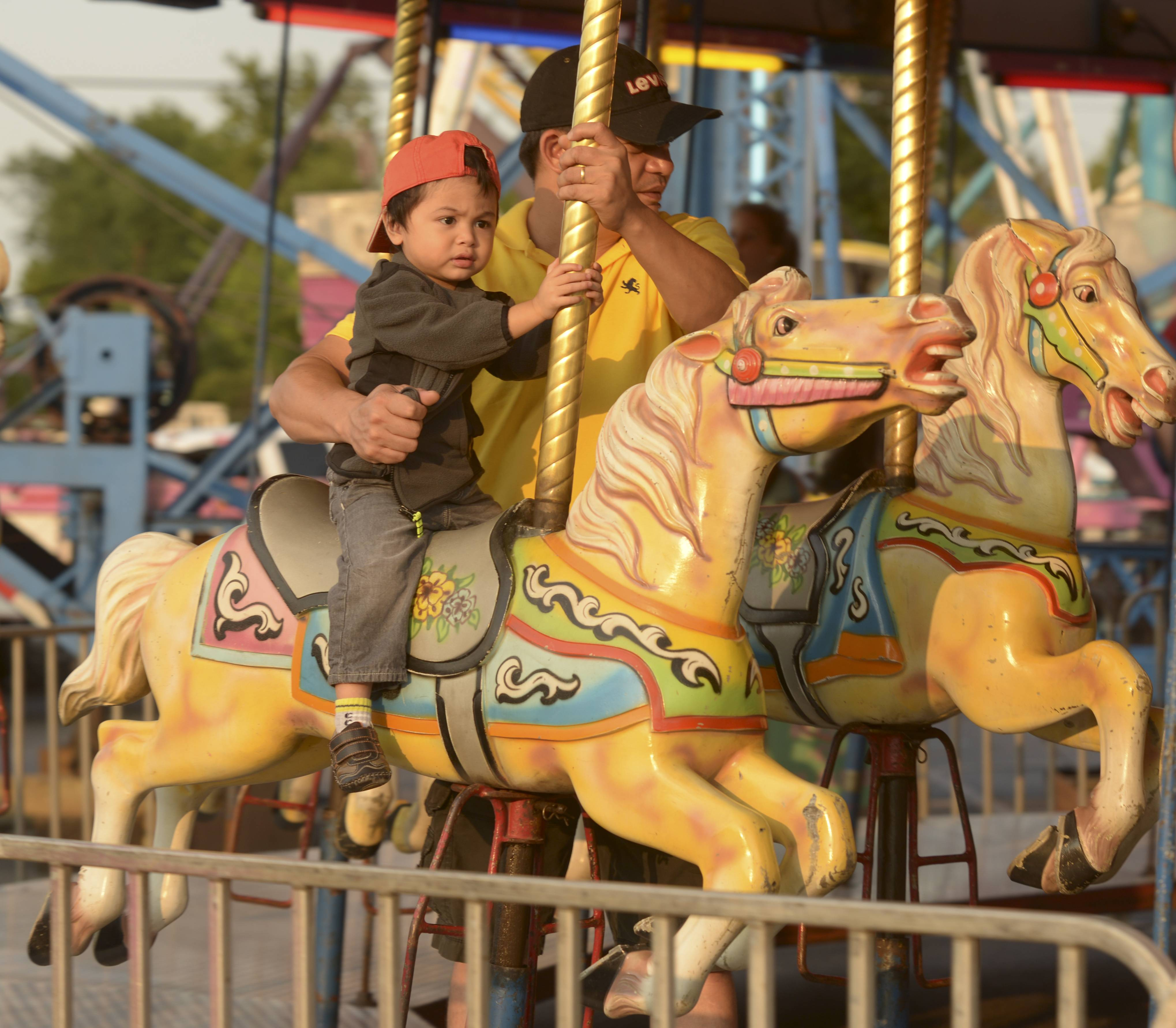 Randy Ocampo of Lombard and his son Jude, 2, ride the carousel at Sacred Heart's annual Germanfest in Lombard. The festival runs through Sunday in the church's parking lot, 114 S. Elizabeth St.