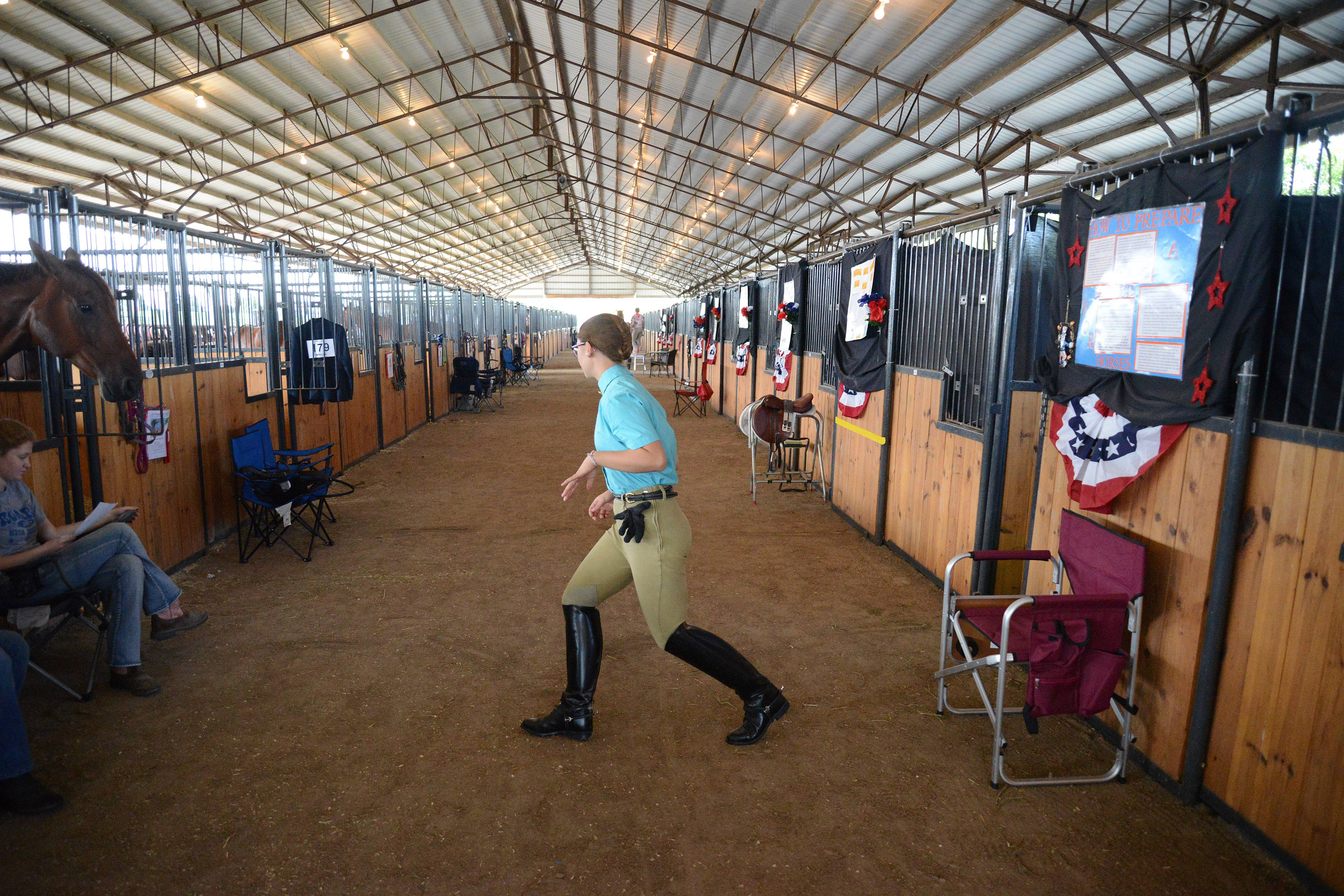Madde Klinkey gallops through her event routine drawn on the floor of the barn while she waits for her class to be called to compete Thursday at the Kane County Fair.