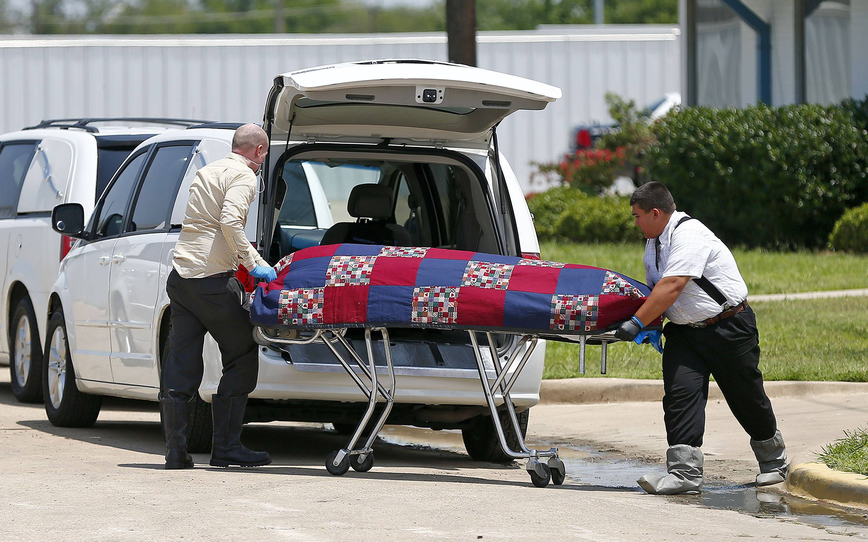 Authorities remove bodies from the Johnson Family Mortuary in east Fort Worth, Texas.