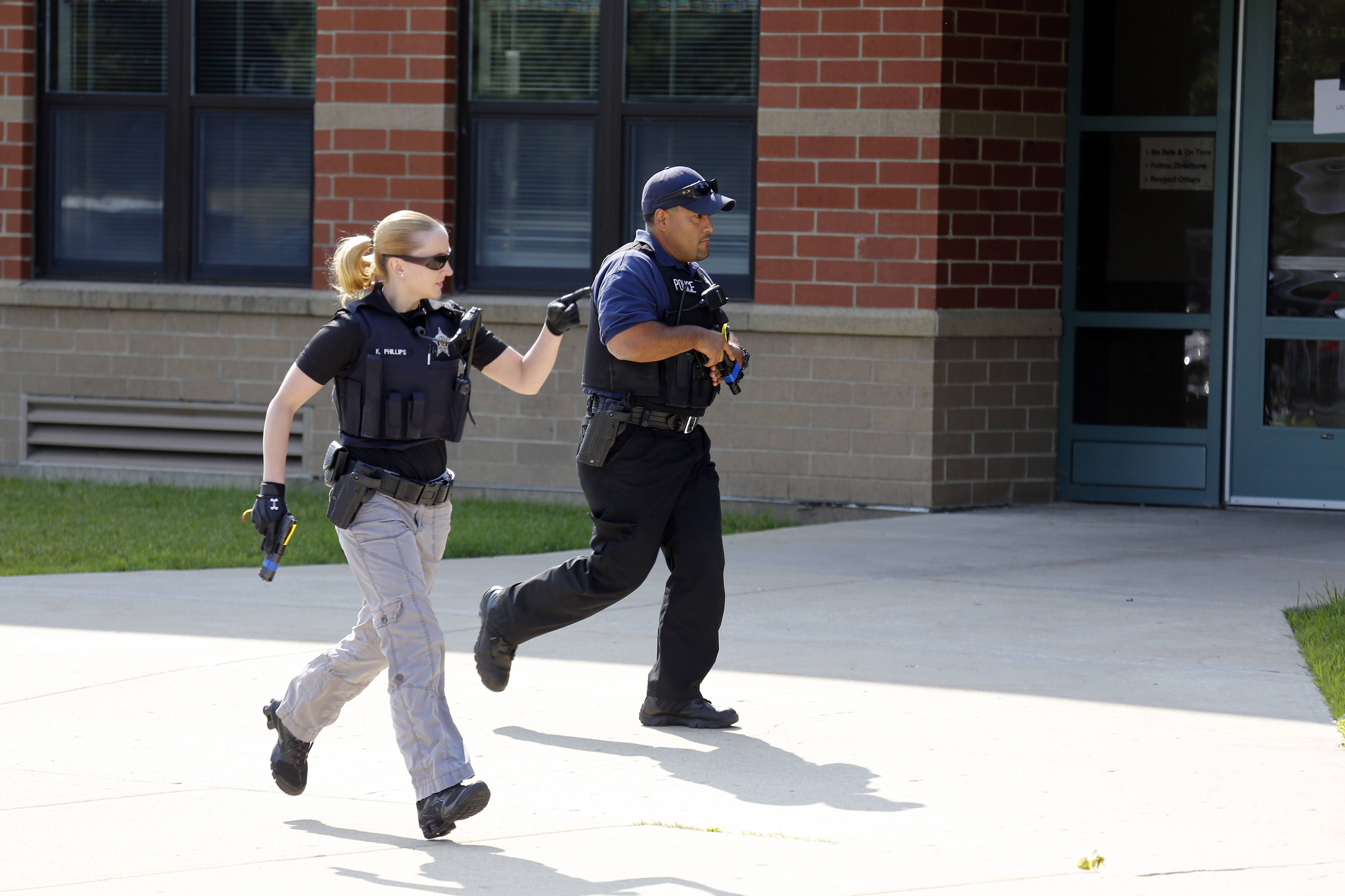 Elgin police officers move into position during Thursday's training at Otter Creek Elementary School. About 200 role players also took part.